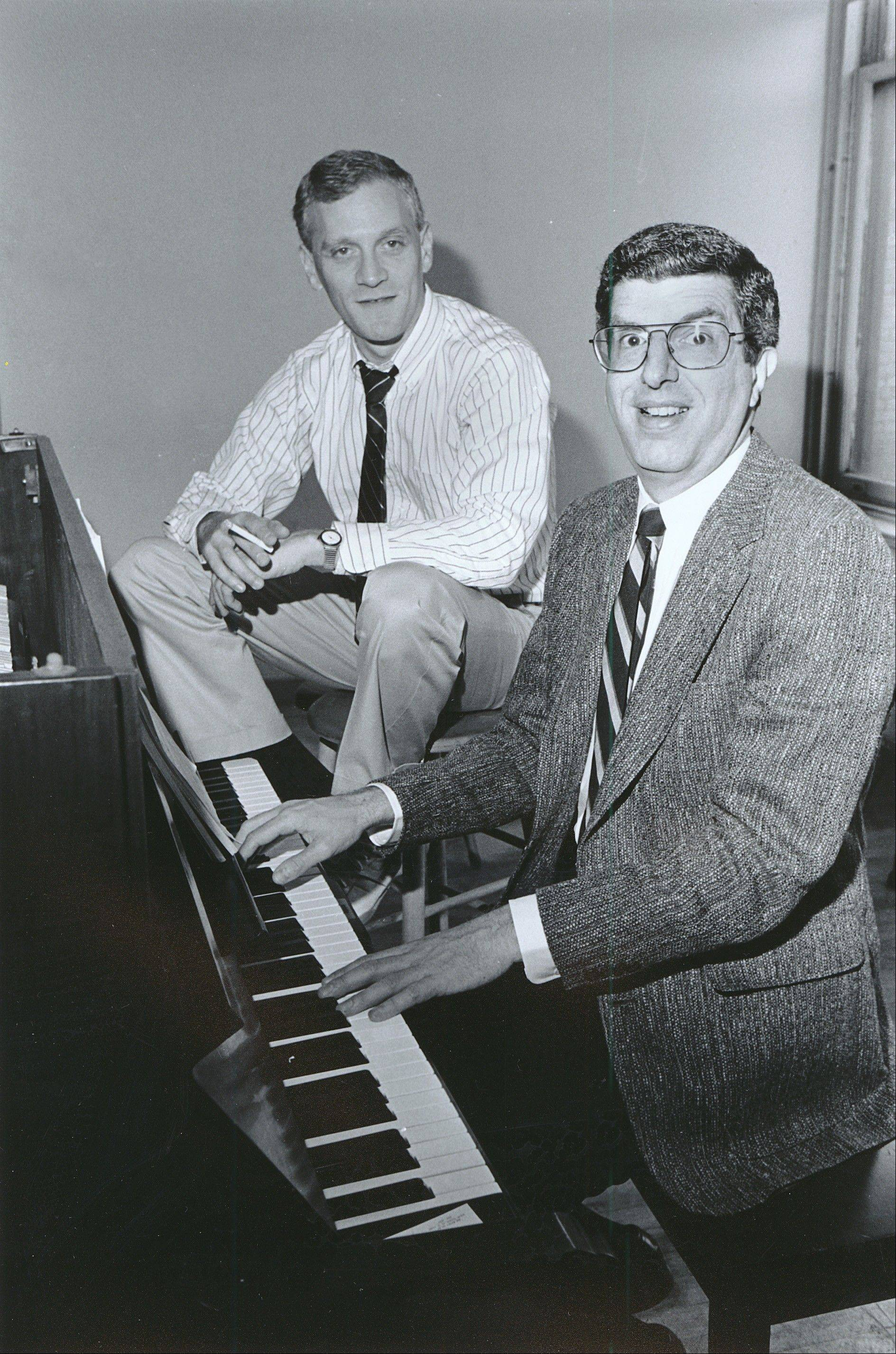 Composer Marvin Hamlisch, right, at the piano worked with lyricist Howard Ashman in 1986. Hamlisch died Monday.