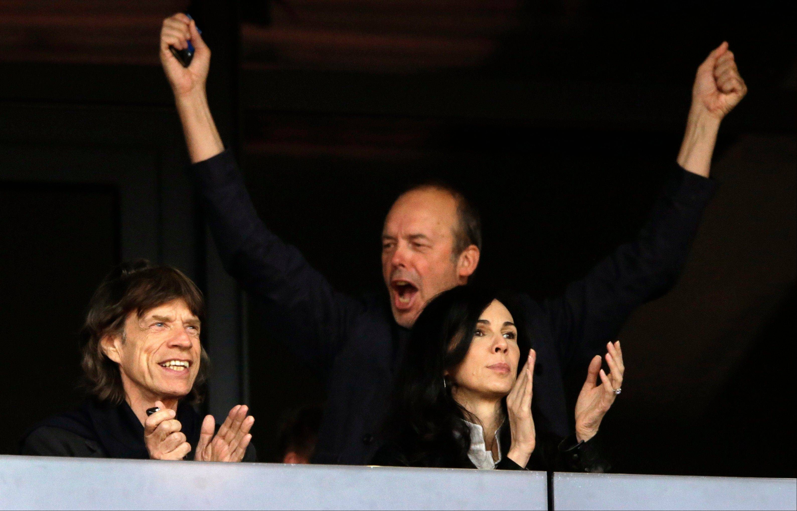 Musician Mick Jagger, left, Monday watches an evening session of athletics competition with L'Wren Scott, right, in the Olympic Stadium at the 2012 Summer Olympics.