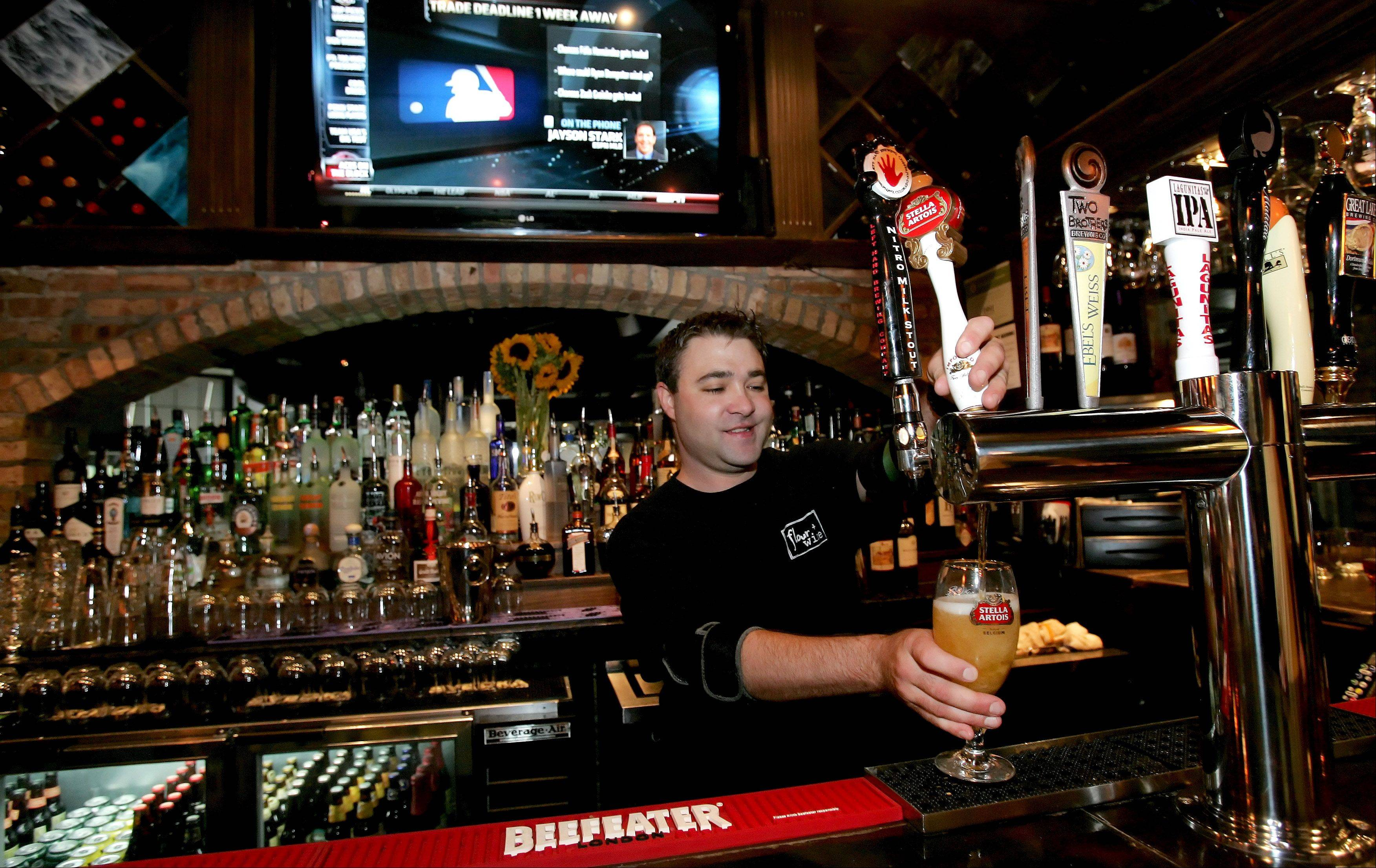 Bartender Michael Archambault pours a beer at Flour + Wine in Glen Ellyn.
