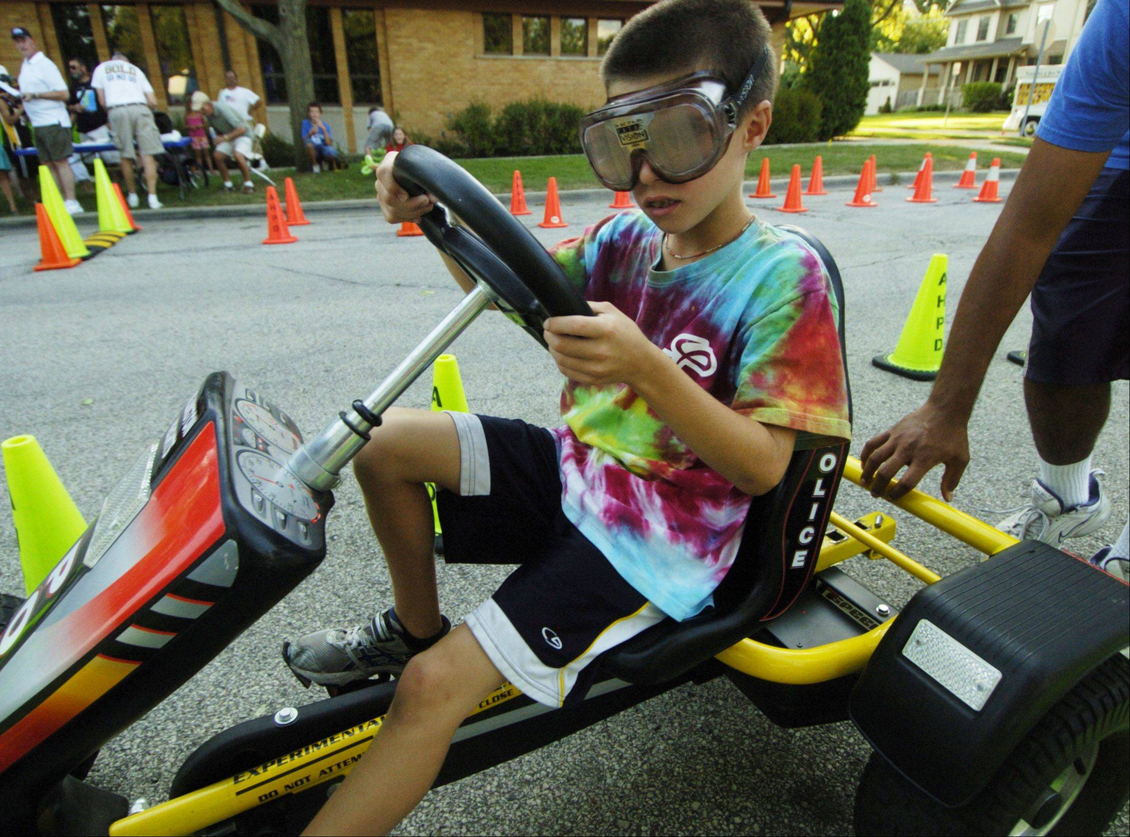 Grayson Hill, 8, of Arlington Heights drives a pedal car while wearing goggles which simulate impairment during Tuesday's National Night Out at North School Park in Arlington Heights.