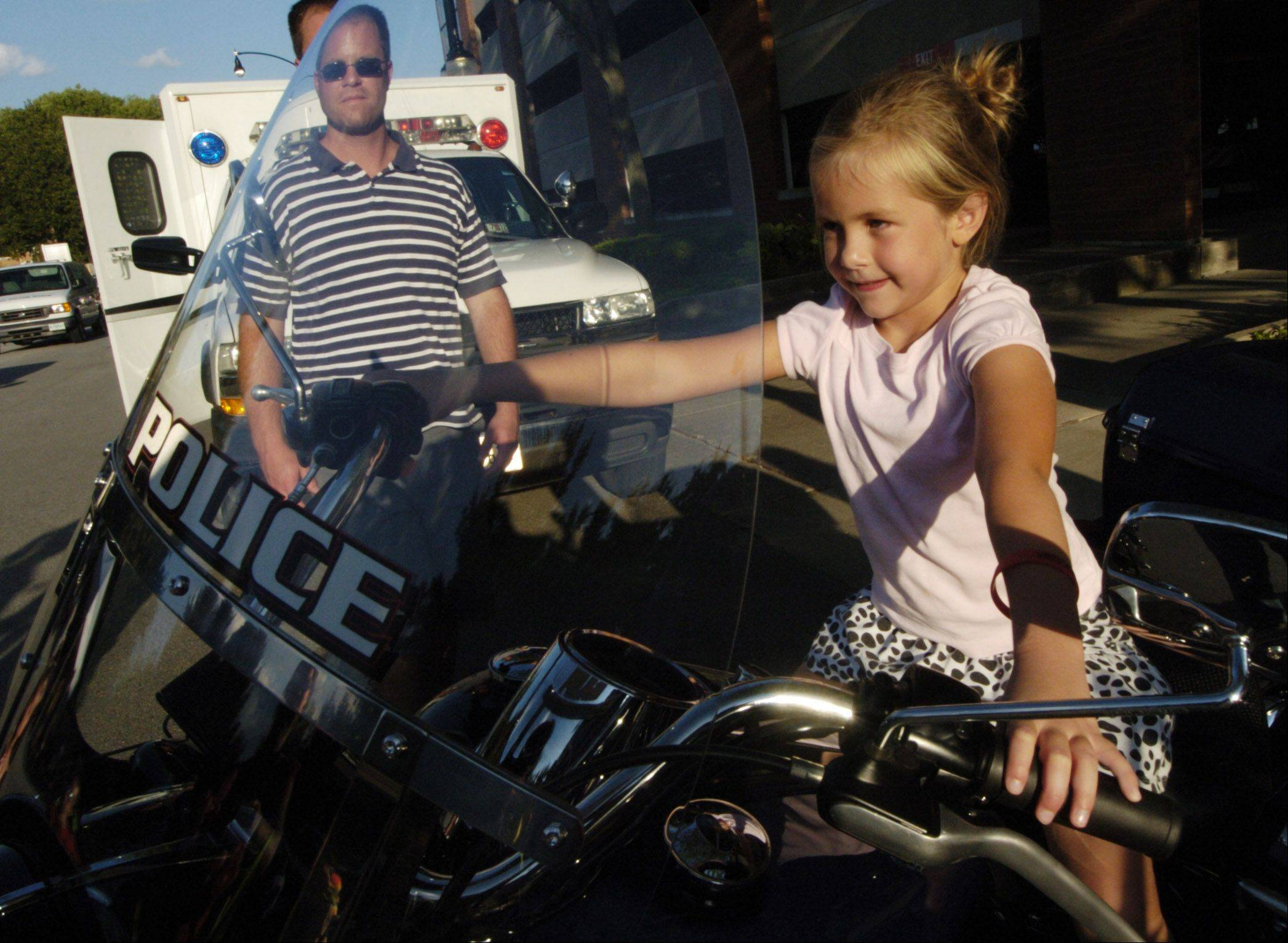 Annie Loring, 6, of Arlington Heights, tries the view from a police motorcycle while attending Tuesday's National Night Out with her family, including her dad, Kevin, at North School Park in Arlington Heights.