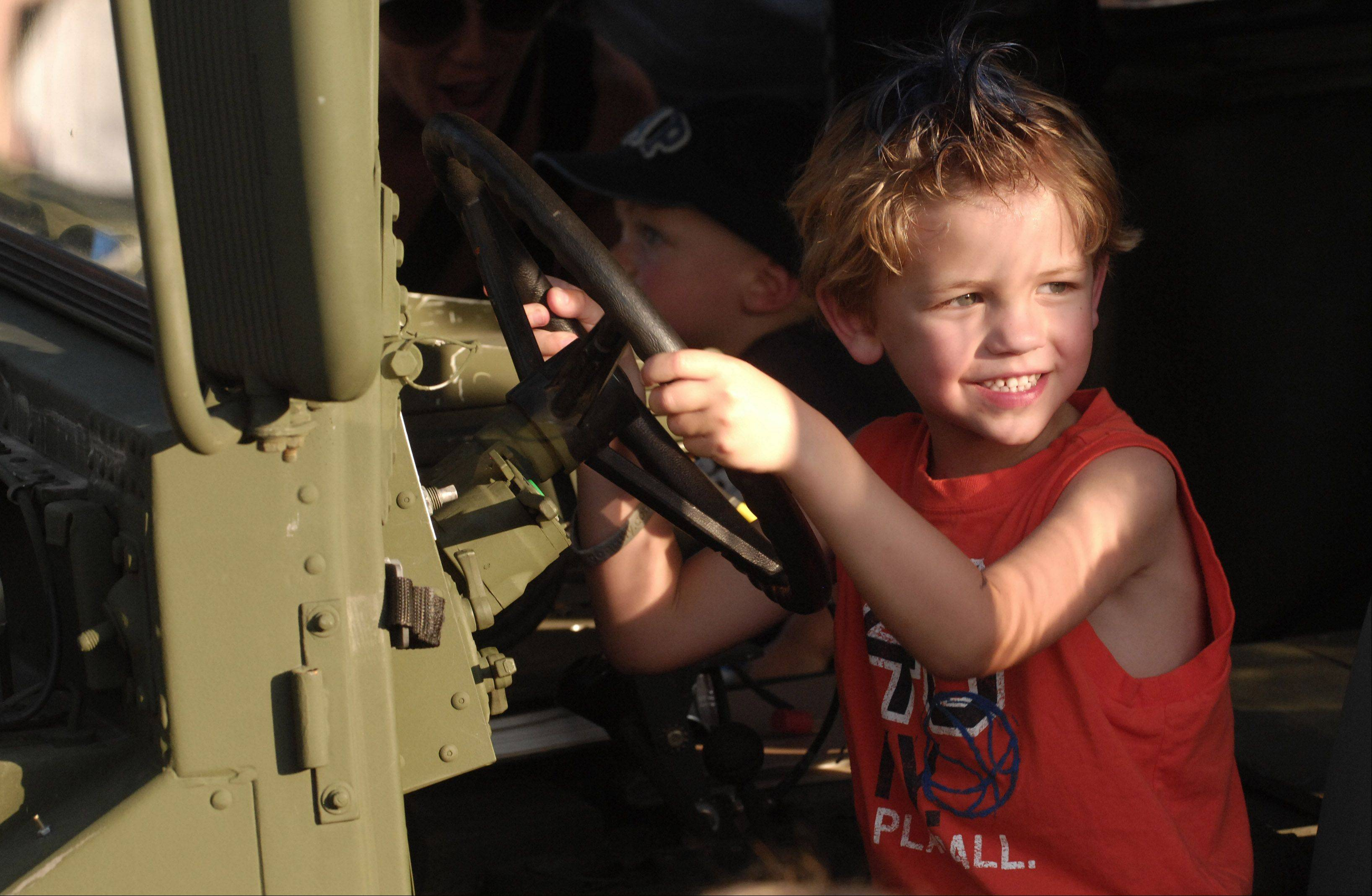 Jack Reed, 5, of Arlington Heights sits in the driver's seat of a military vehicle during Tuesday's National Night Out at North School Park in Arlington Heights.