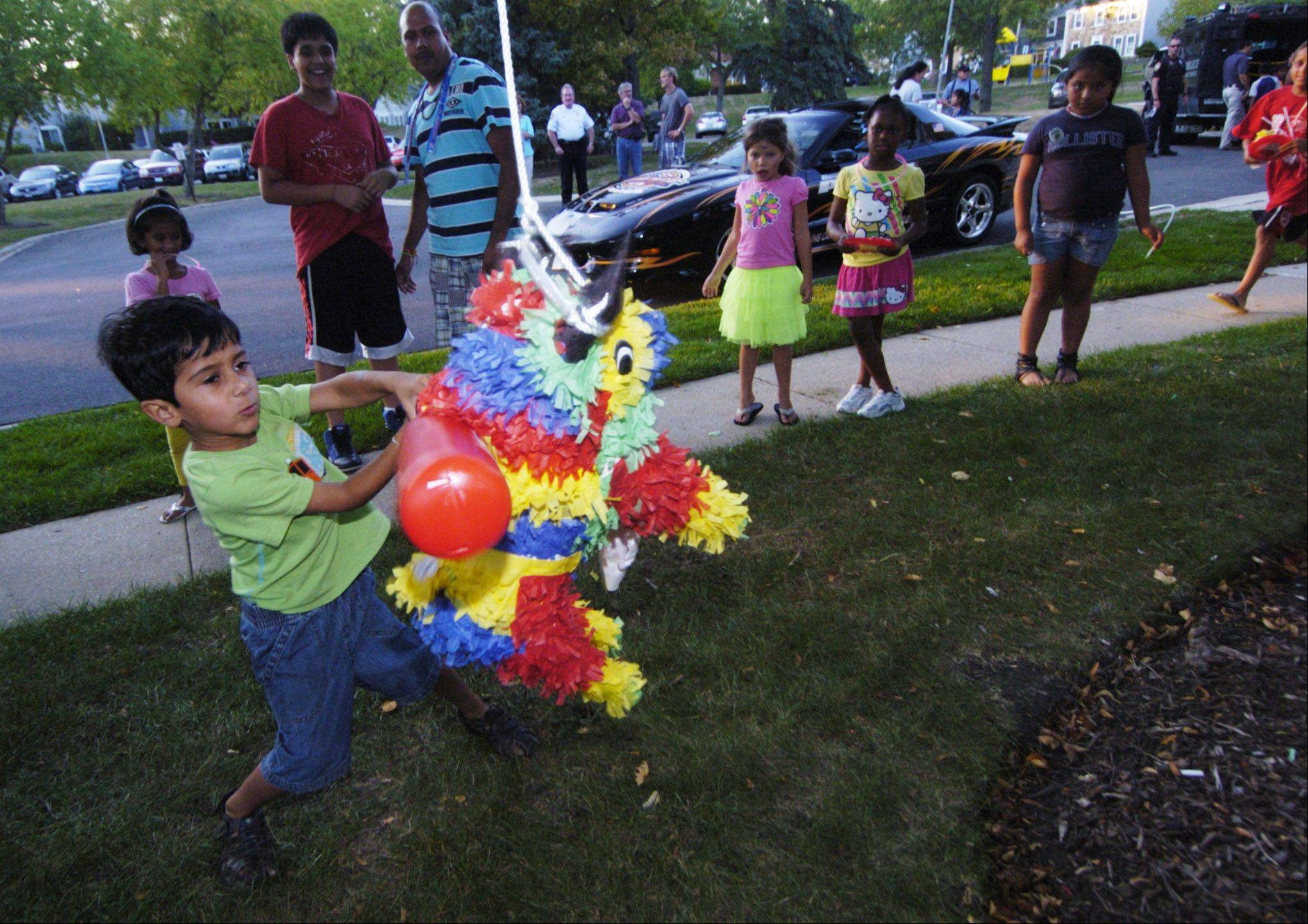 Akshar Rao, 4, of Hoffman Estates takes a swing at a pinata during Tuesday's National Night Out event near Williamsburg Drive in Hoffman Estates.
