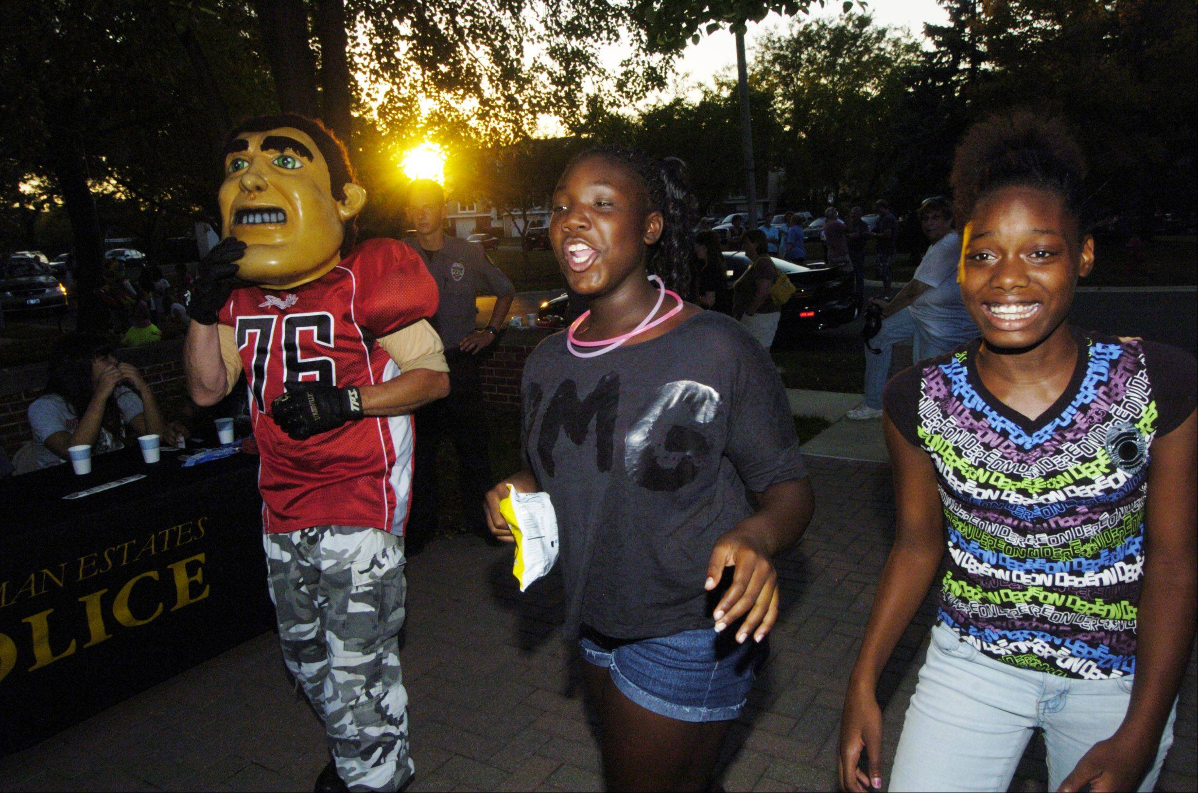 "Jada Smith, 13, center, and Sammarion Dungey, 12, both of Hoffman Estates have fun with the mascot ""Sarge"" of the Chicago Slaughter during Tuesday's National Night Out event in Hoffman Estates."