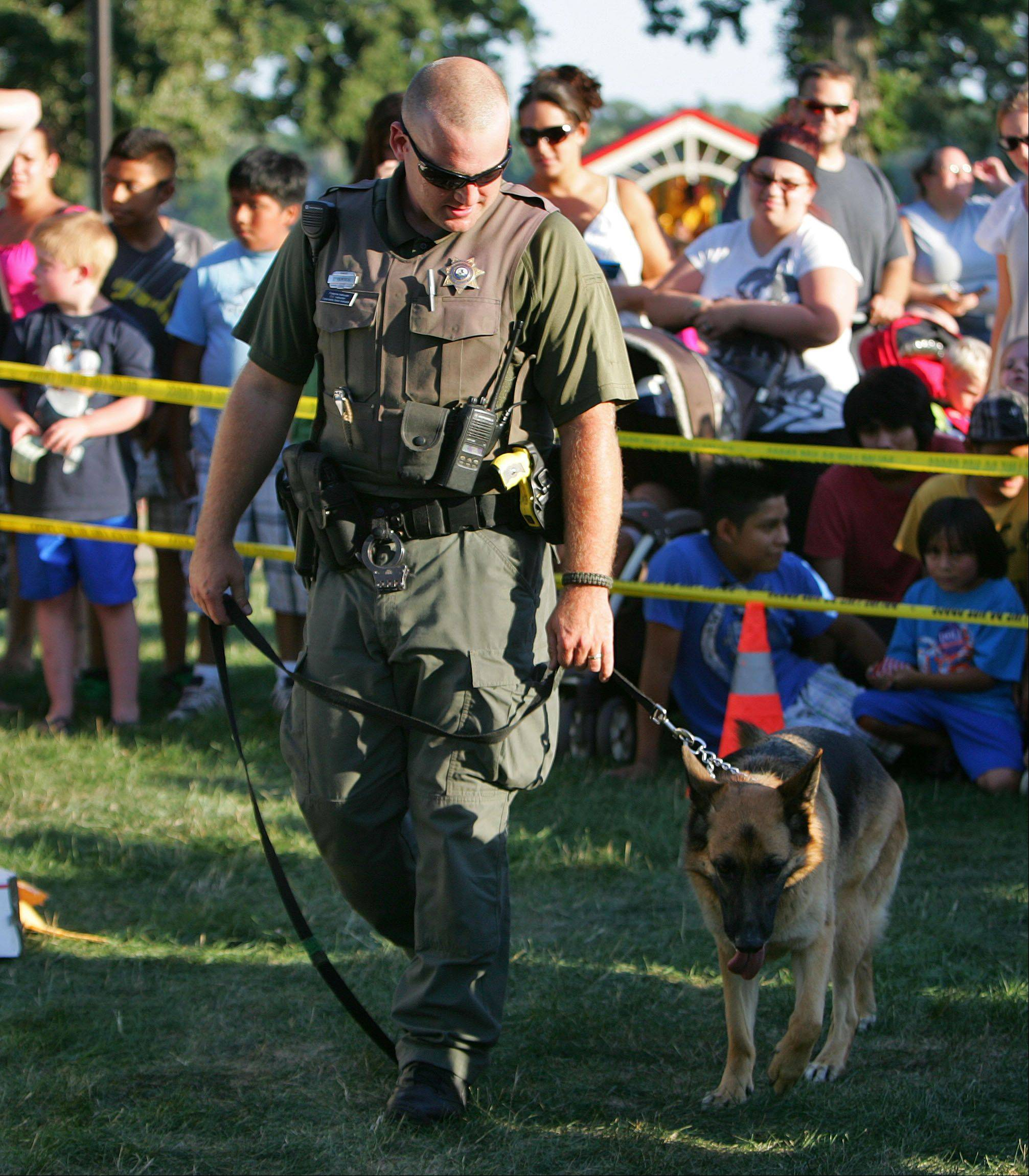 Round Lake Area Park District Ranger Terry Kaminski shows off his search dog Nadja during a demonstration at the Round Lake Beach Police Department National Night Out event at the Round Lake Beach lakefront Tuesday.