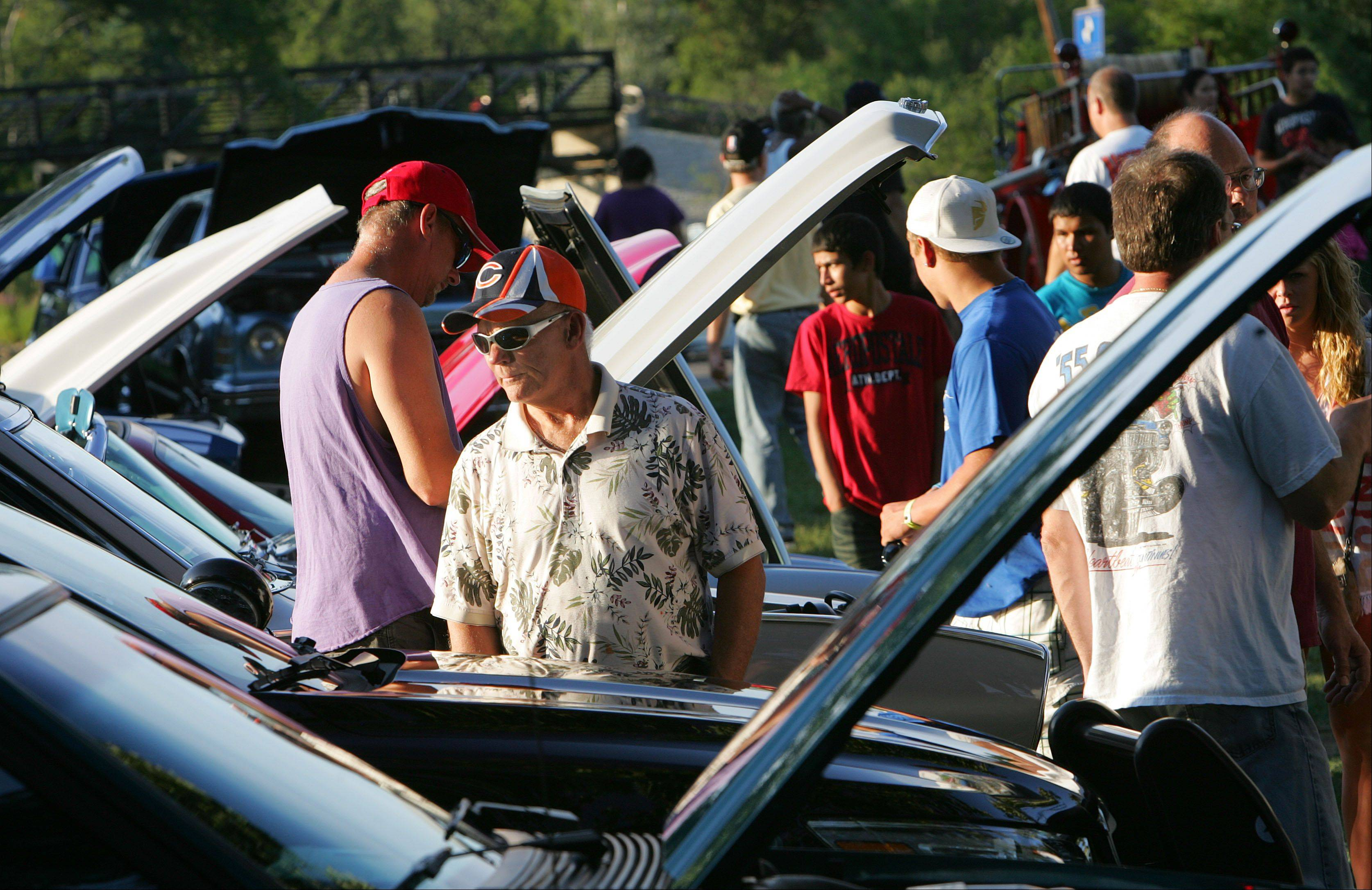 People peruse classic and fancy modern vehicles at a car show during the Round Lake Beach Police Department's National Night Out event at the Round Lake Beach lakefront Tuesday.