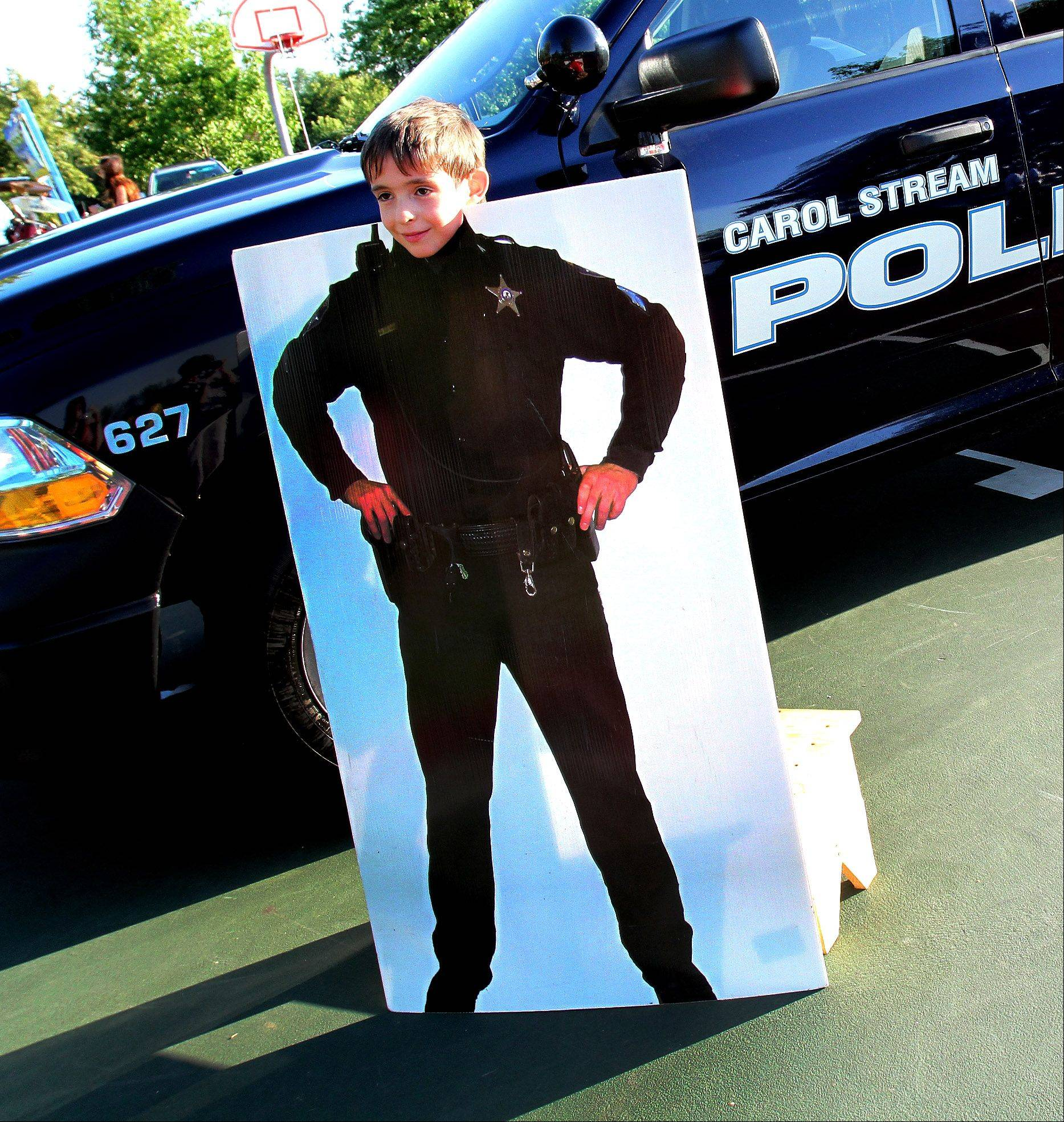 Andre Lind, 6, of Carol Stream, poses in a police officer cutout as part of the National Night Out at Community Park in Carol Stream on Tuesday.