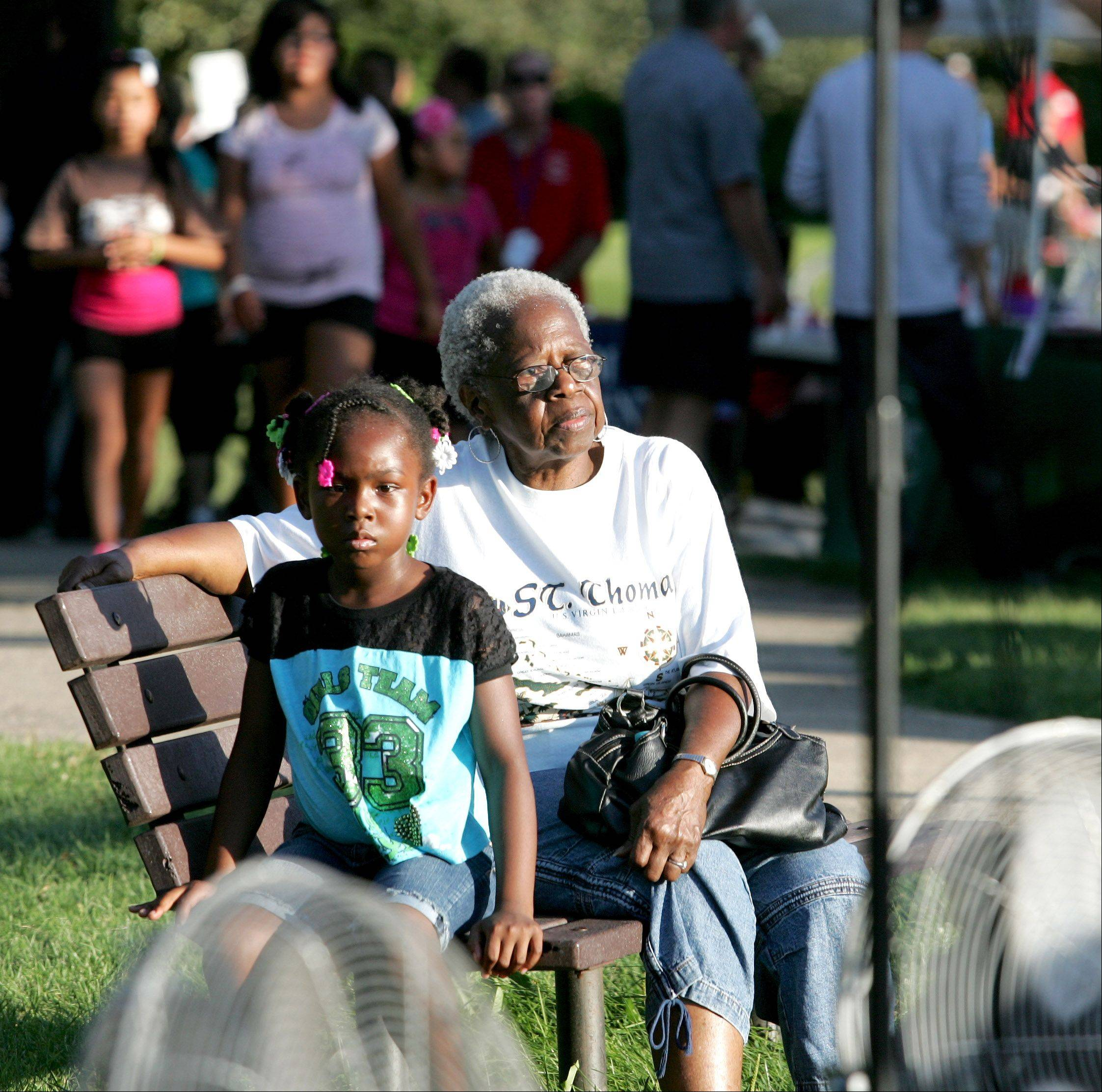 Lucille Moore of Carol Stream and her great-granddaughter, Jamee Clements, 6, listen to the band Serendipity during National Night Out at Community Park in Carol Stream on Tuesday.
