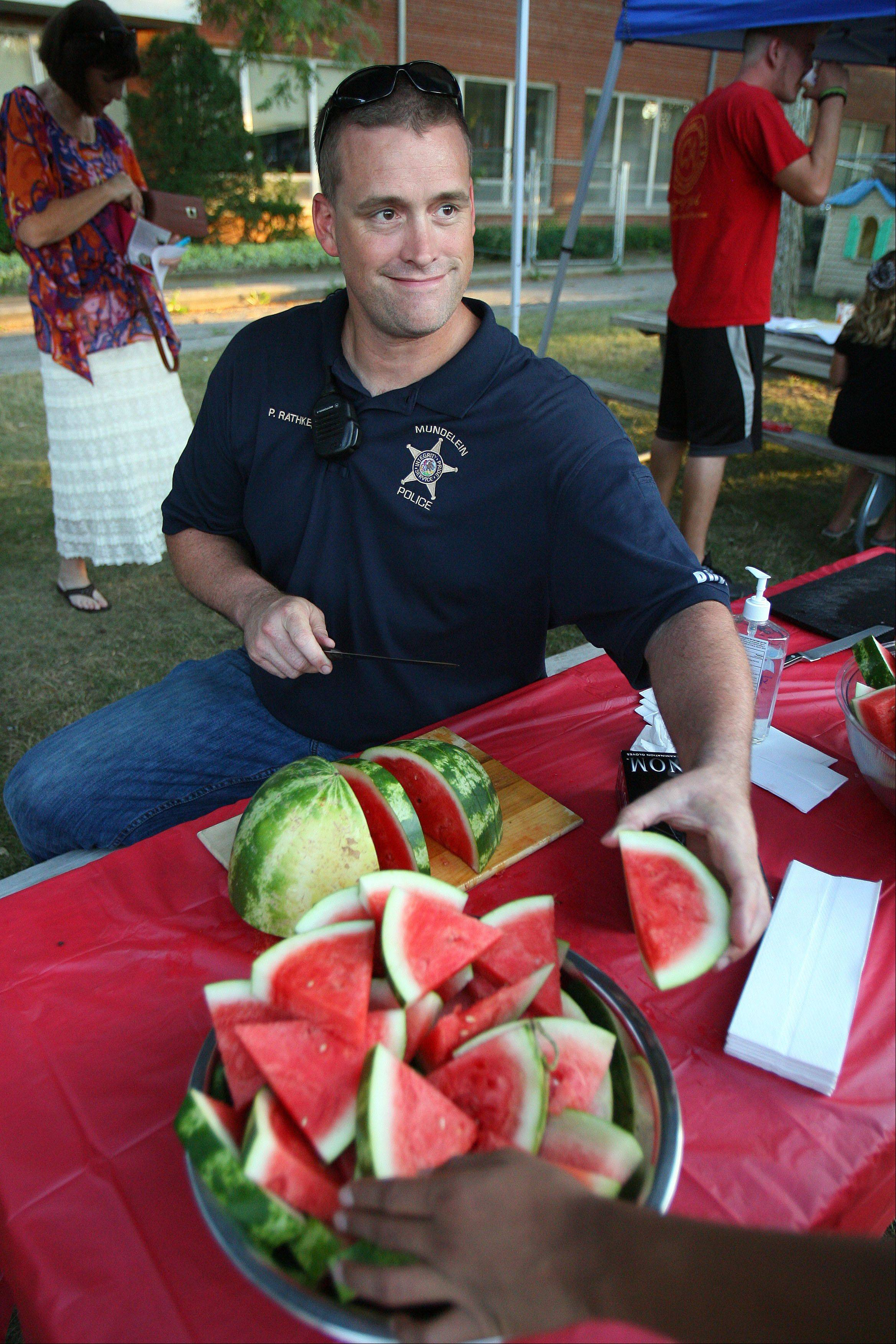 Mundelein Police officer Phil Rathke offers watermelon during a National Night Out event at Santa Maria del Popolo Catholic Church in Mundelein Tuesday night.