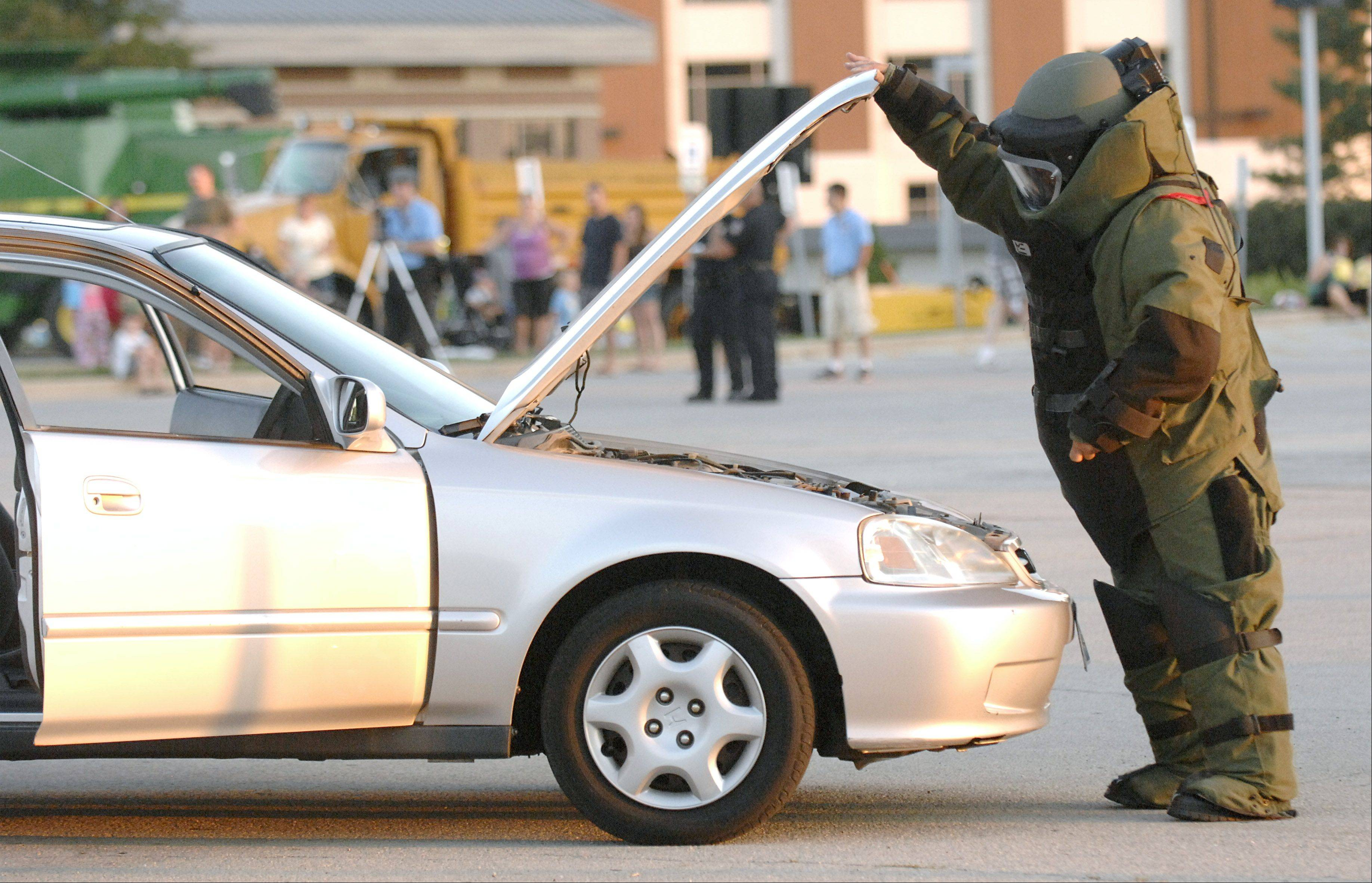 A member of the Kane County Sheriff Bomb Squad checks under the hood of a car during a bomb investigation demonstration at the Kane County Sheriff's National Night Out.