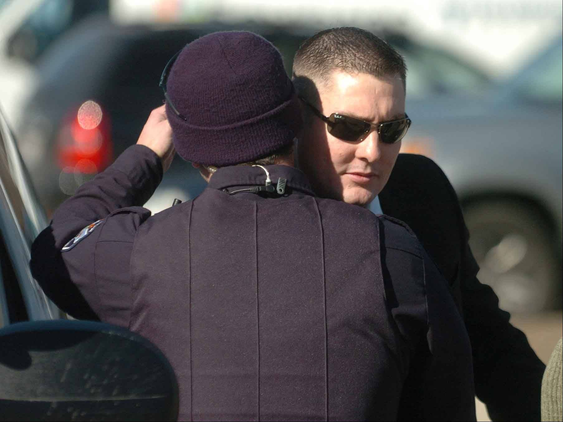 Oak Brook police officer Andrew Franczak says goodbye to Stephen Peterson after Peterson was dismissed from the force in February 2011.