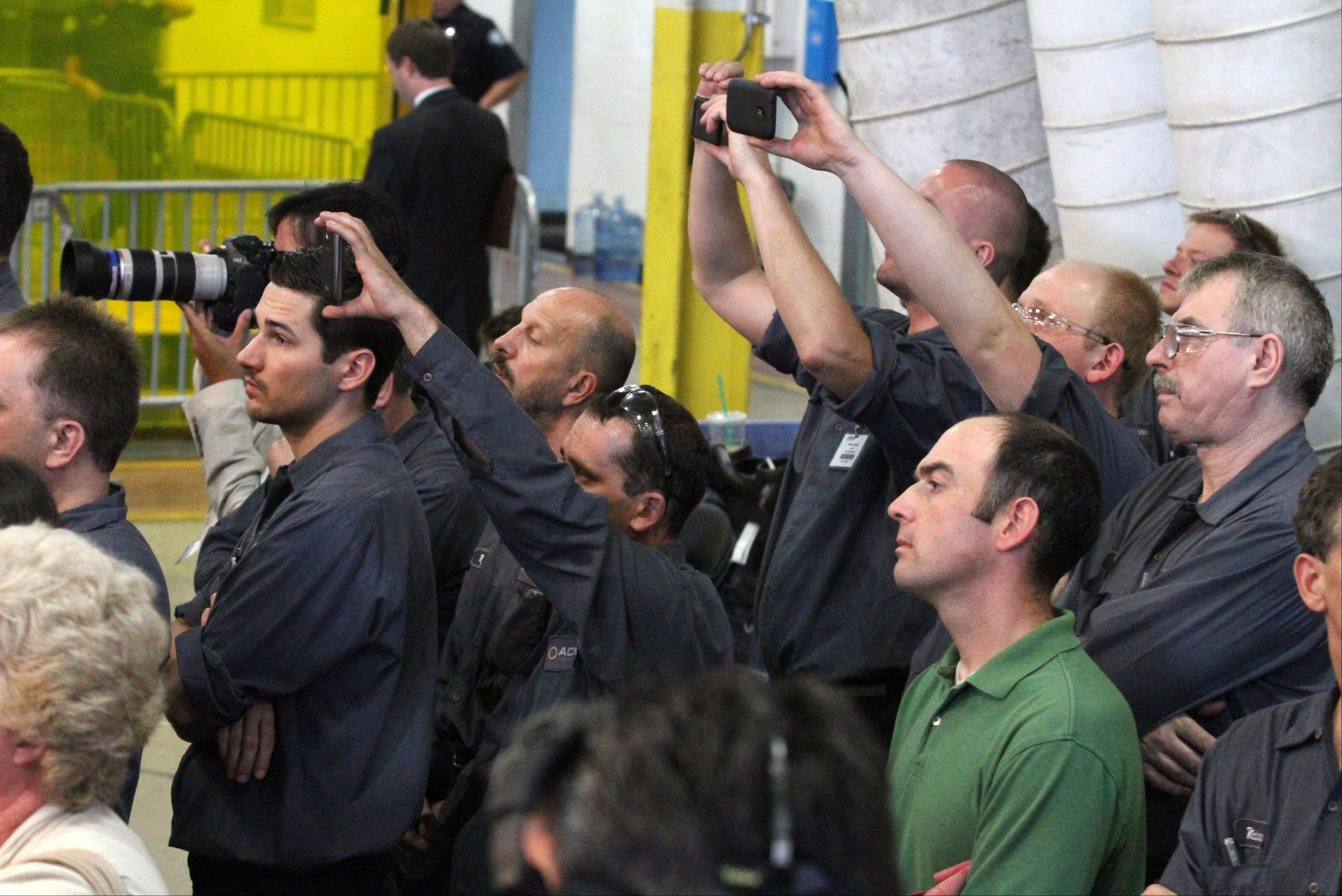Workers at Acme Industries takes cellphone photographs as GOP Presidential candidate Mitt Romney speaks at the company in Elk Grove Village on Tuesday, August 7.