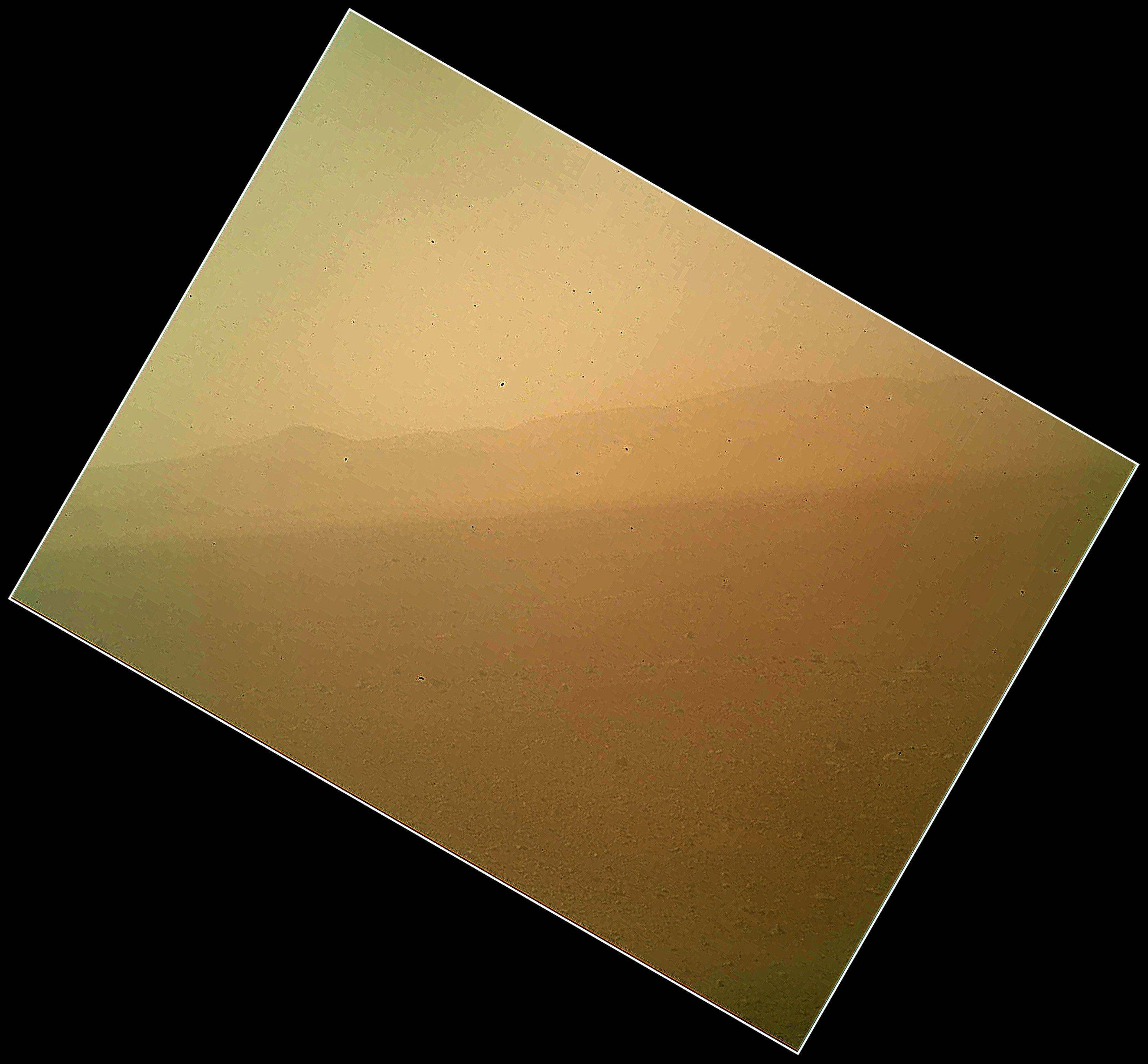 This is the first color view of the north wall and rim of Gale Crater where NASA's rover Curiosity landed Sunday night. The picture was taken by the rover's camera at the end of its stowed robotic arm and appears fuzzy because of dust on the camera's cover.