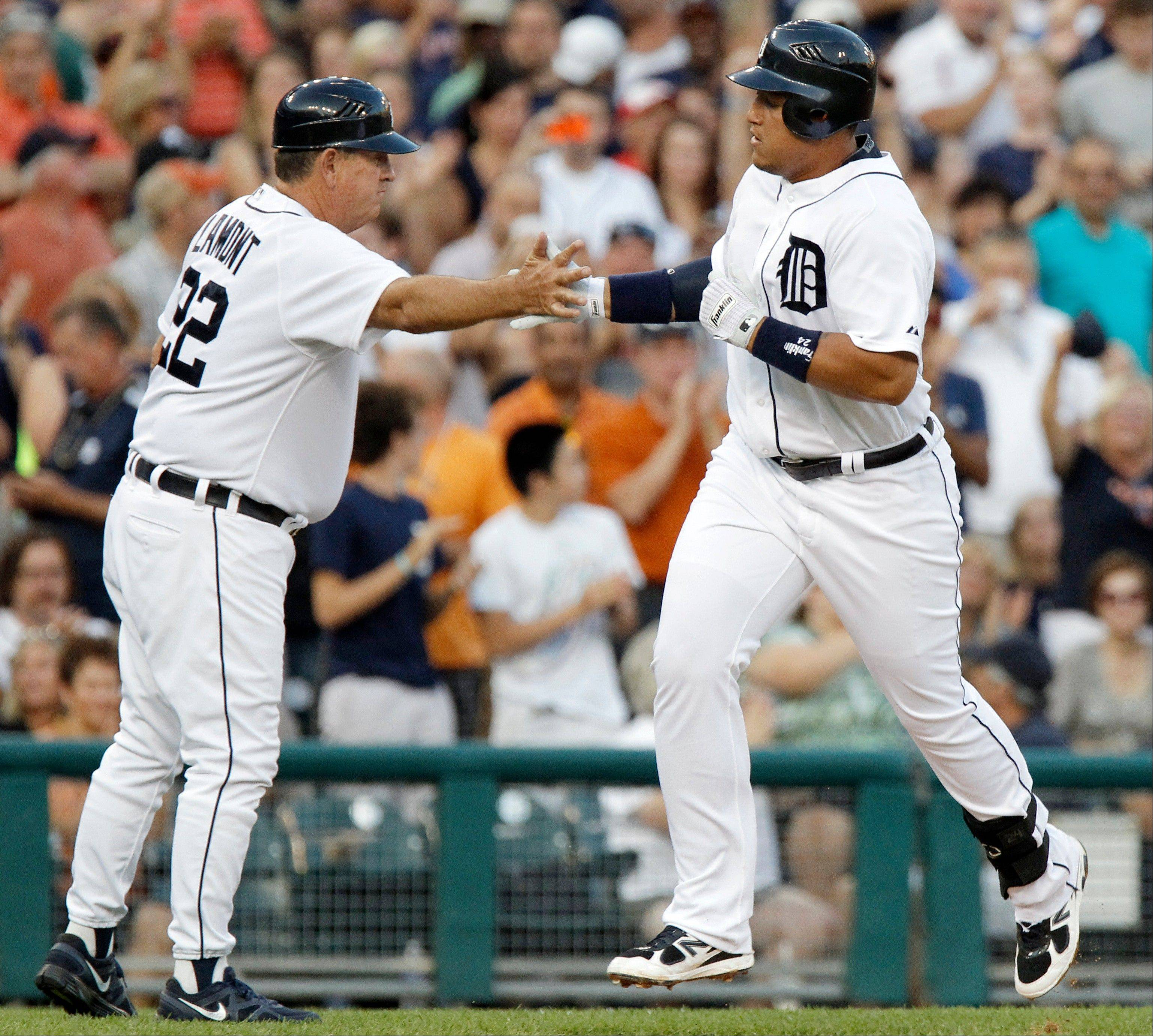 Tigers third base coach Gene Lamont congratulates Miguel Cabrera on his solo home run in the fourth inning Tuesday at home against New York.