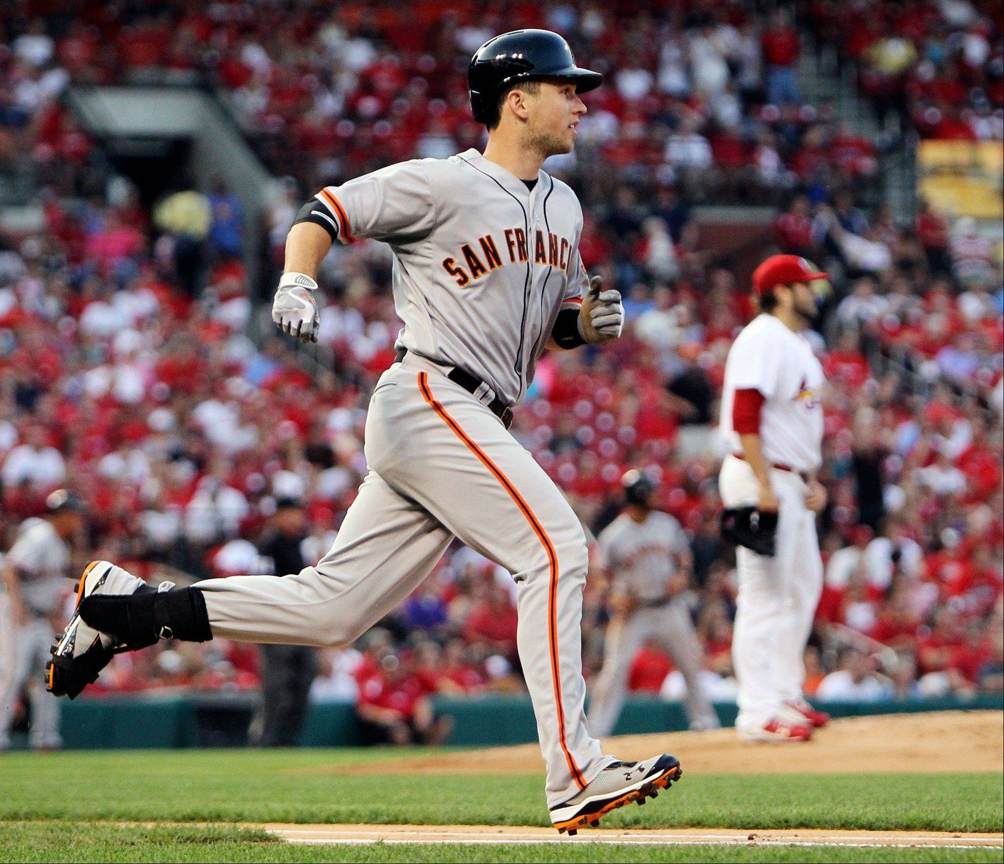 The Giants' Buster Posey rounds the bases after hitting a three-run home run off Cardinals starting pitcher Lance Lynn in the first inning Tuesday in St. Louis.
