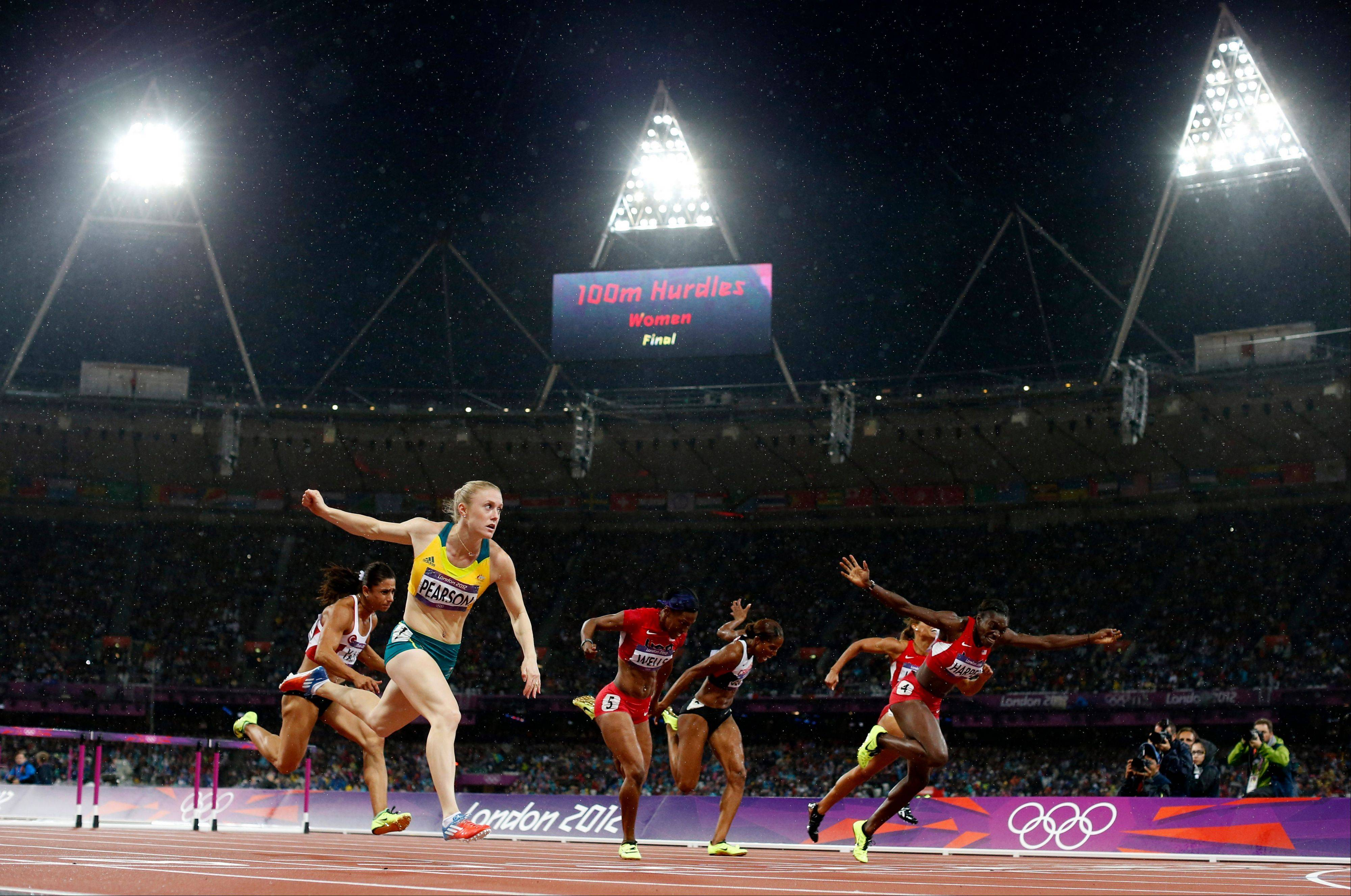 Australia's Sally Pearson, front left, crosses the finish line to win gold ahead of United States' Dawn Harper, front right, in the women's 100-meter hurdles final Tuesday.