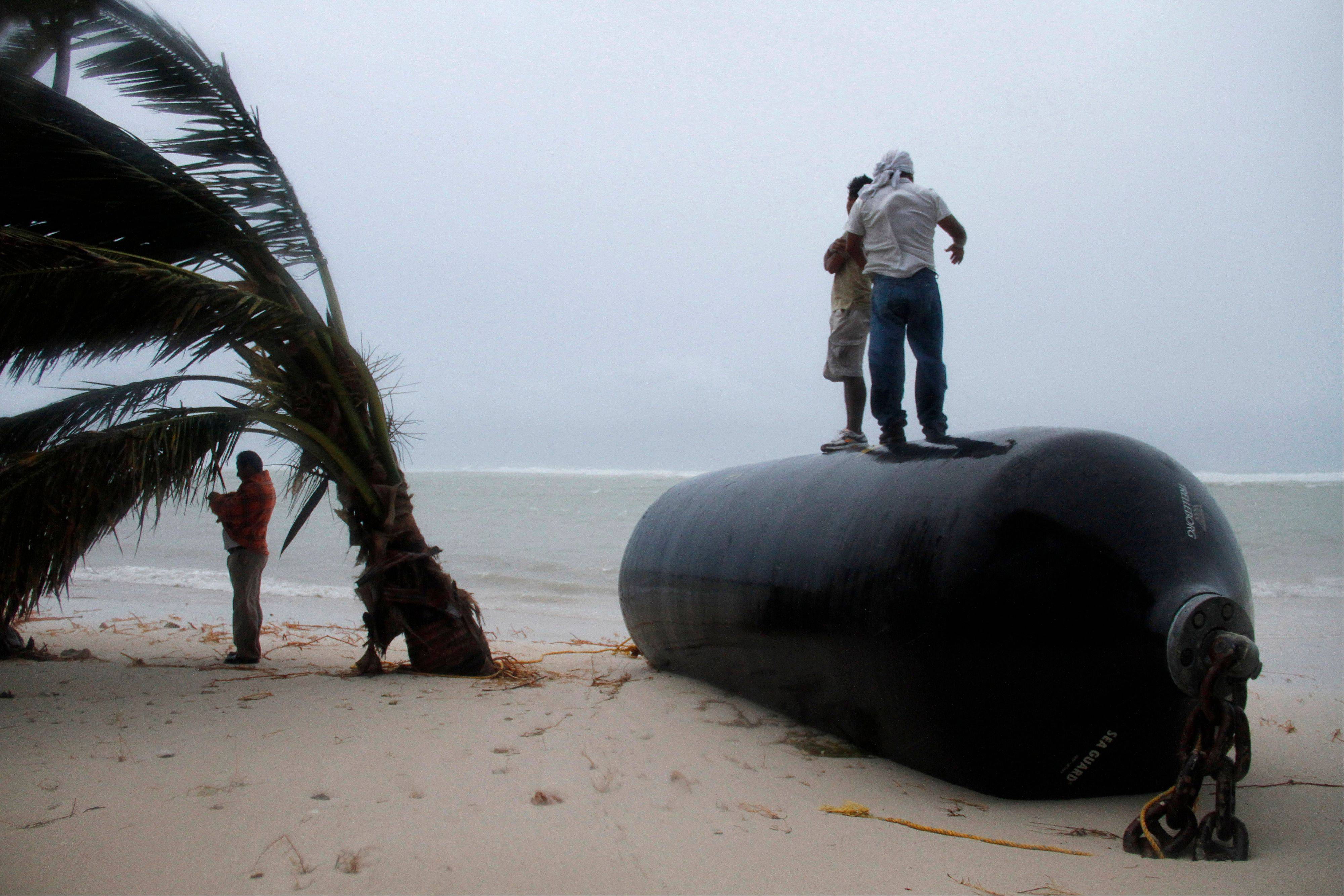 Men stand on top of a marine fender that was ripped from a dock after Hurricane Ernesto made landfall overnight in Mahahual, near Chetumal, Mexico, Wednesday.