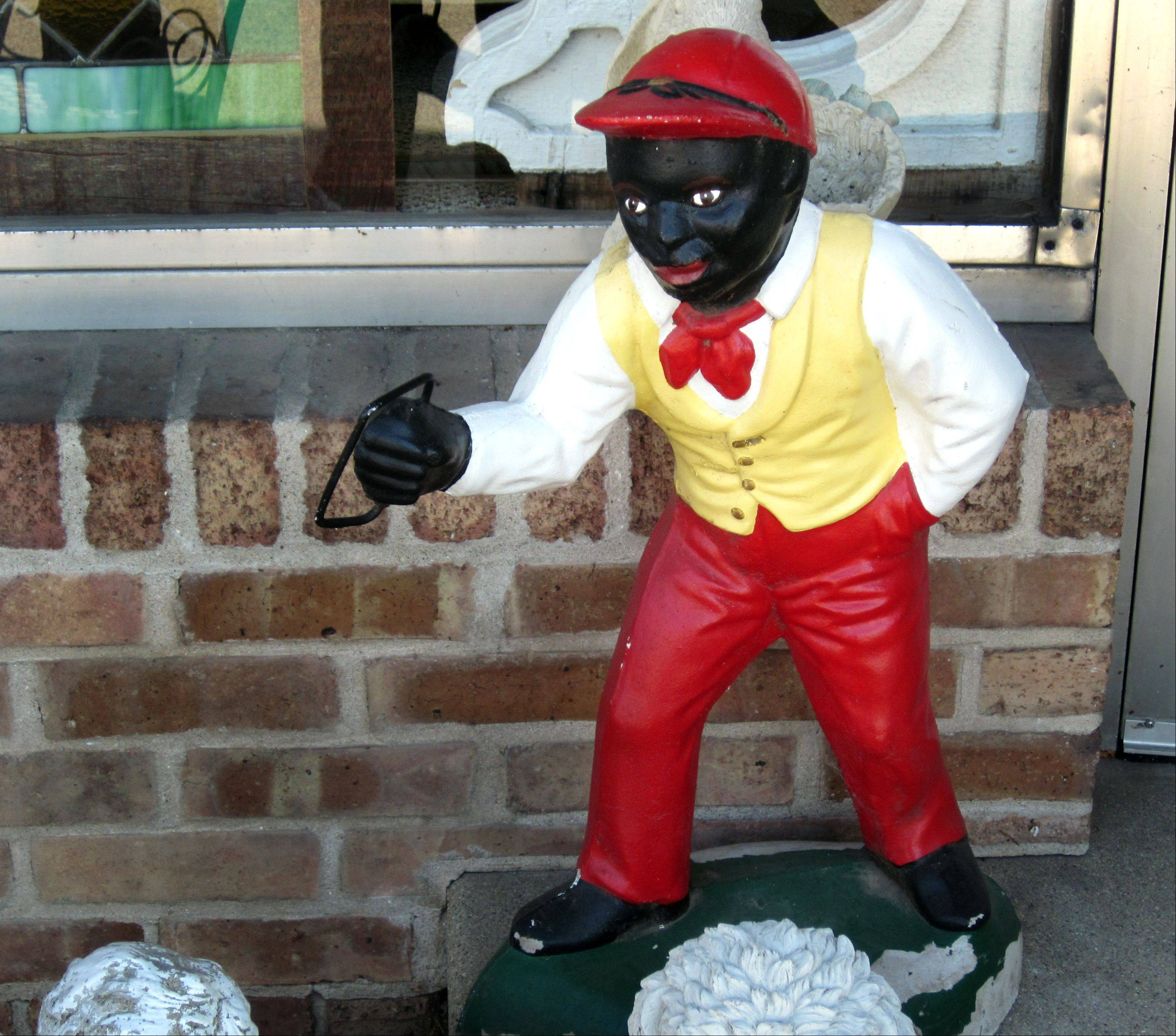 This lawn jockey statue in front of Tivoli Garden Antiques in downtown Barrington has sparked debate over whether it's a racist caricature or it honors the positive role such statues played in marking houses participating in the Underground Railroad.