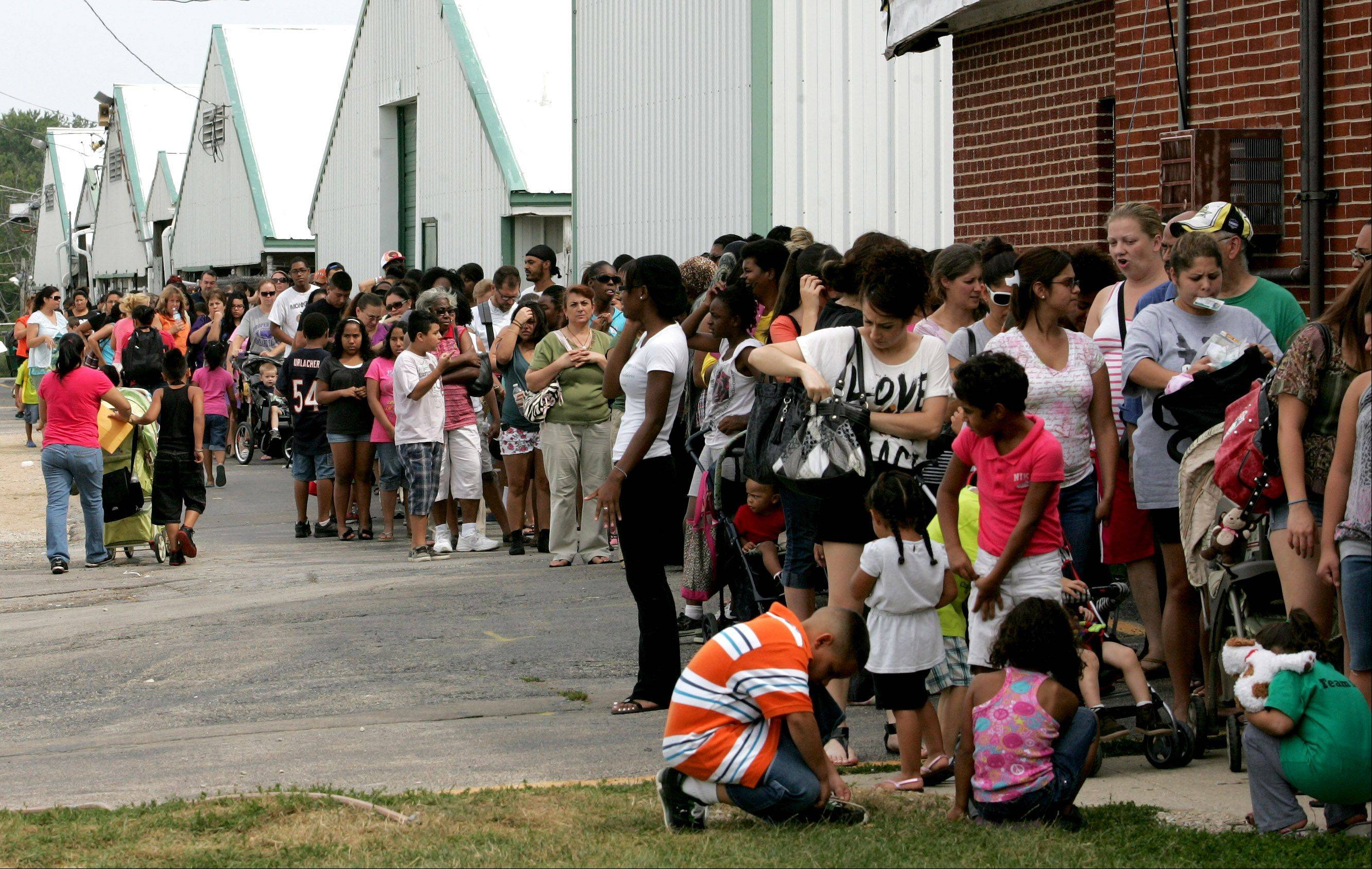 "Hundreds line up Wednesday at the DuPage County Fairgrounds in Wheaton to attend Catholic Charities' Back to School Fair. ""It gives them resources they might not otherwise have,"" said Deloris Walker, human resources coordinator with Catholic Charities."