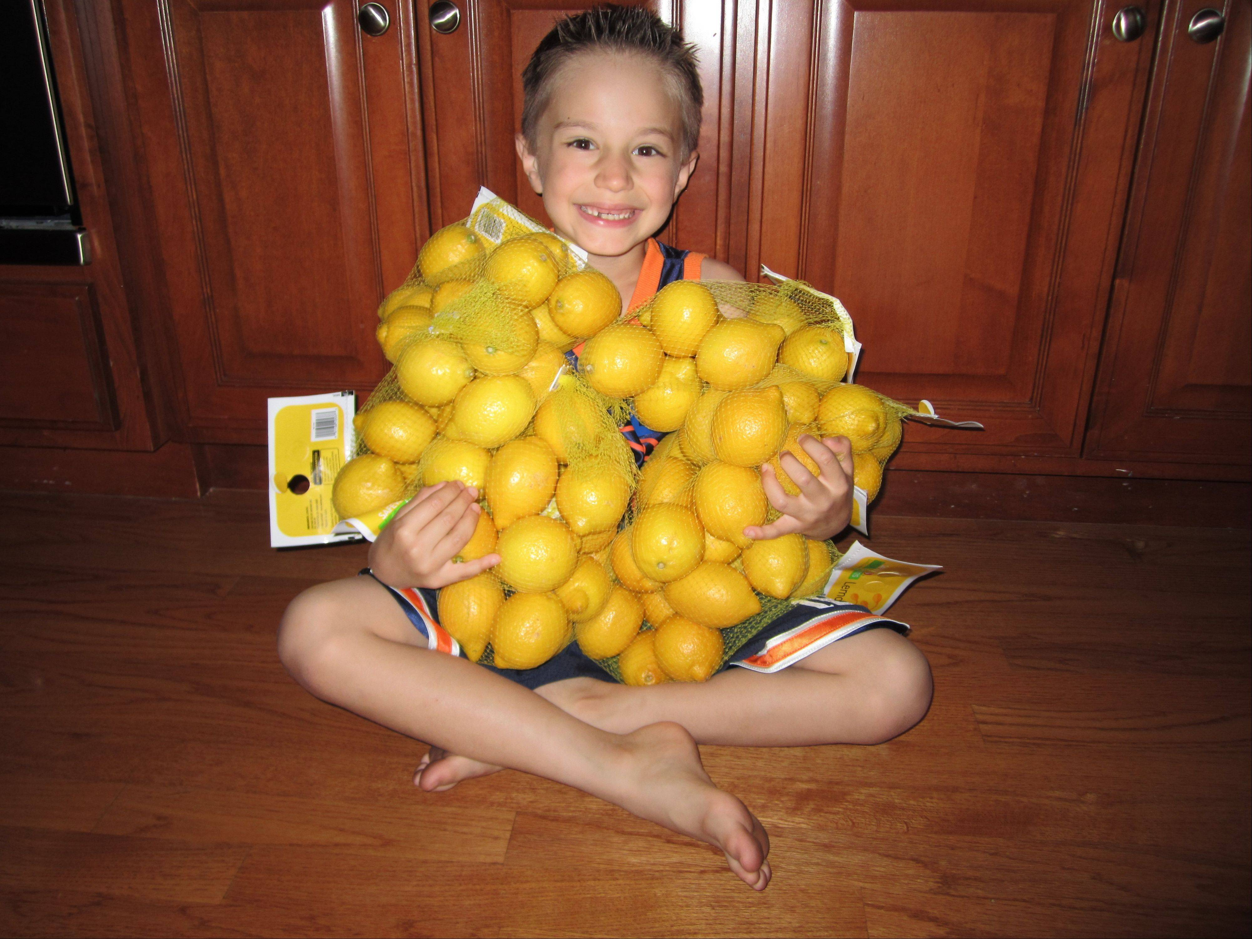 Six-year-old Luke Hasan of Naperville holds the bags of lemons that helped him raise more than $2,100 for the clean water project by opening a LemonAIDE stand.