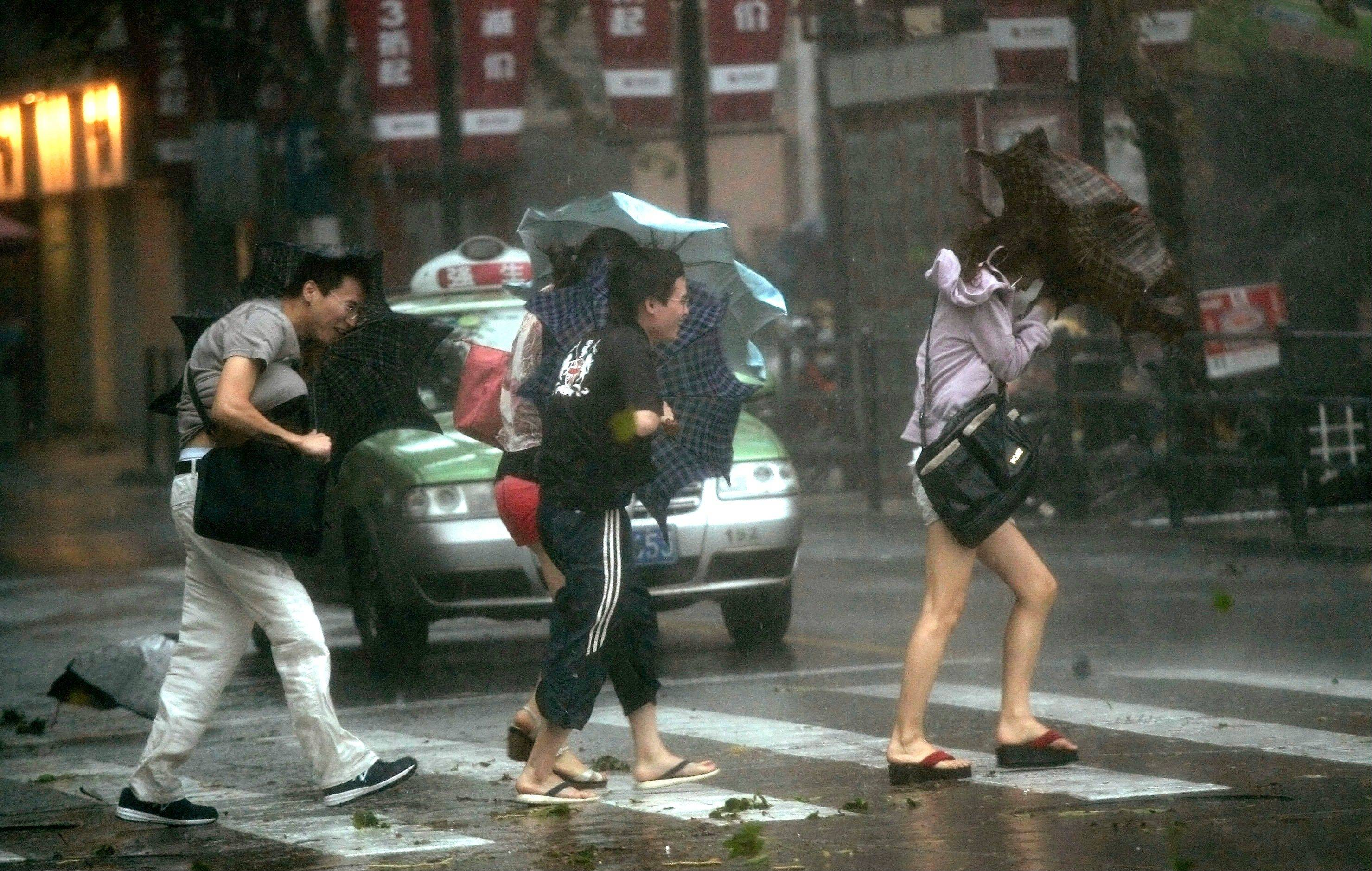 People walk in a rainstorm brought on by Typhoon Haikui Wednesday Aug. 8, 2012 in Shanghai, China. The typhoon slammed into eastern China's Zhejiang province early Wednesday, packing winds up to 90 miles per hour and triggering flooding.