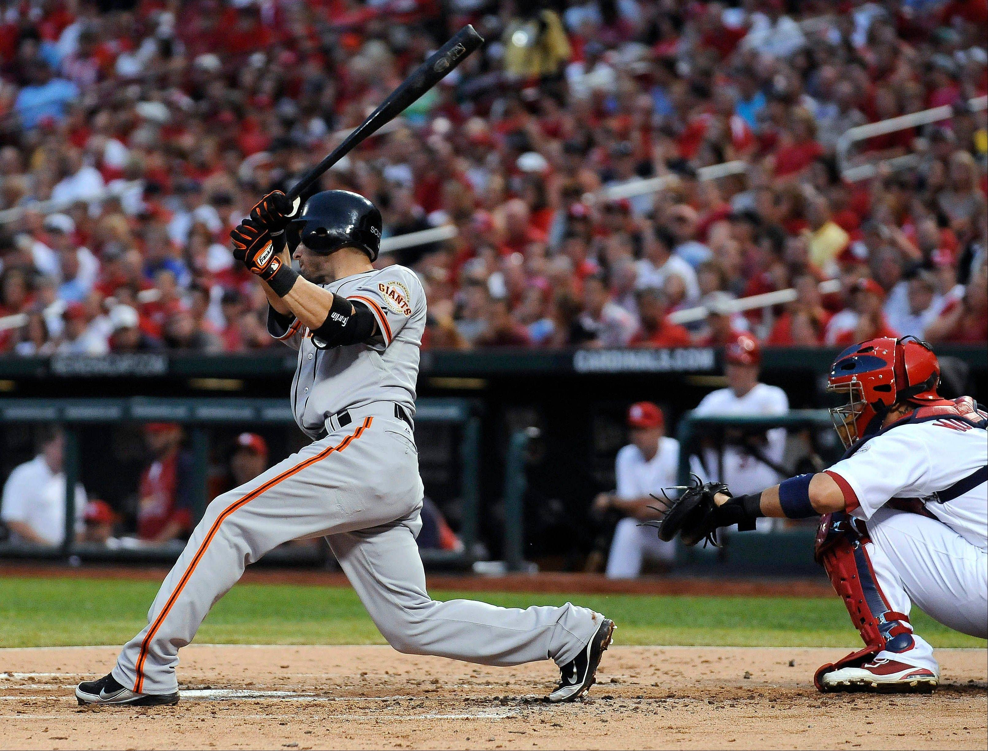 San Francisco's Marco Scutaro hits an RBI single during the third inning Wednesday in St. Louis. He followed with a two-run double in the eighth and a grand slam in the ninth.