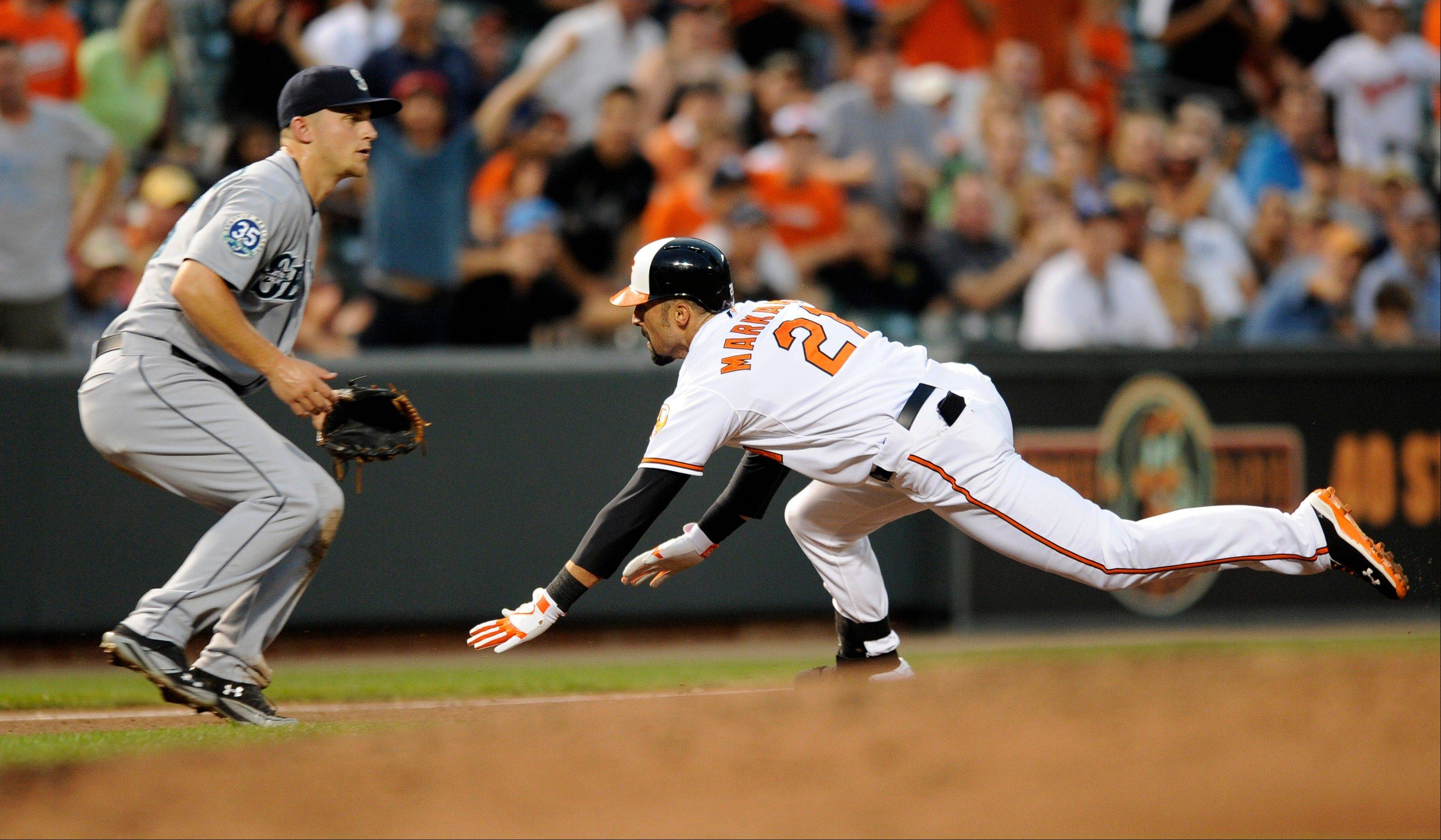 The Orioles' Nick Markakis heads for third on a triple as Seattle Mariners third baseman Kyle Seager waits for the ball during the third inning Wednesday in Baltimore.