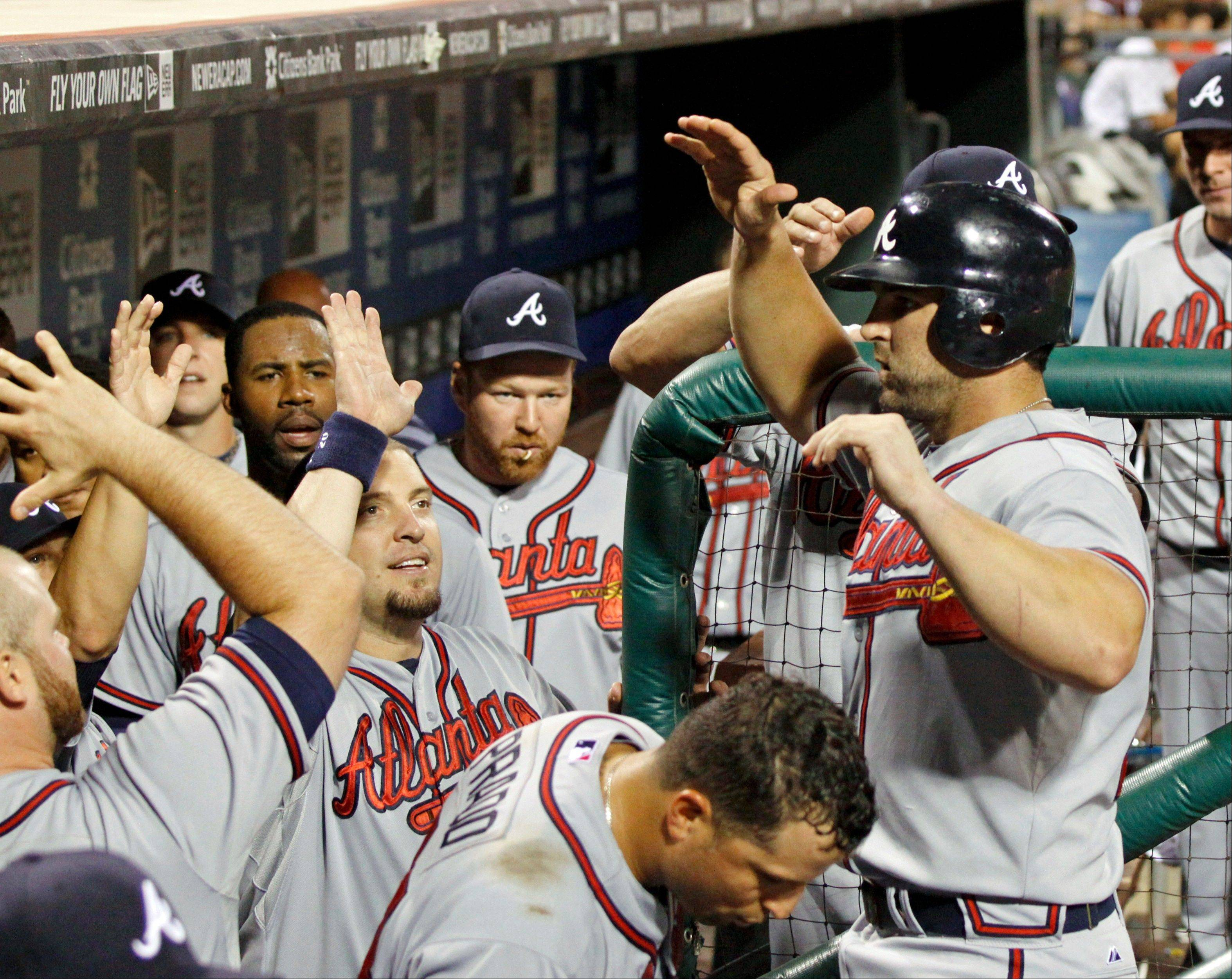 Atlanta's Dan Uggla, right, celebrates with teammates after scoring against the Phillies in the seventh inning Wednesday in Philadelphia.