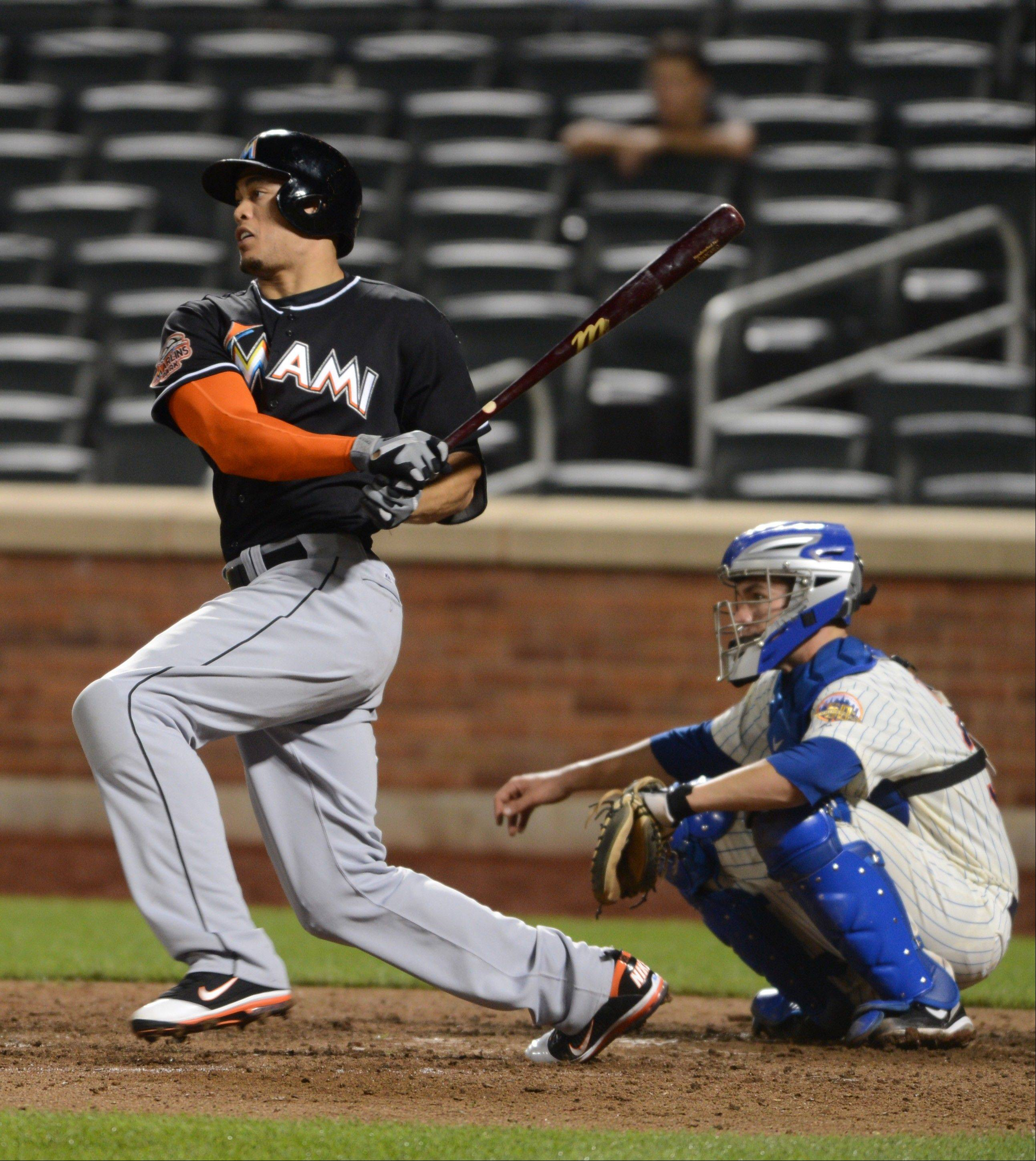 The Marlins' Giancarlo Stanton singles in the ninth inning Wednesday against the New York Mets in New York.
