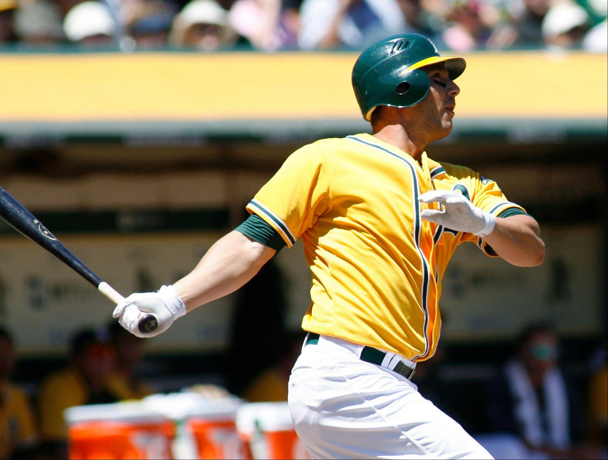 The Oakland Athletics' George Kottaras follows through on a two-run home run against the Los Angeles Angels Wednesday during the second inning in Oakland, Calif.