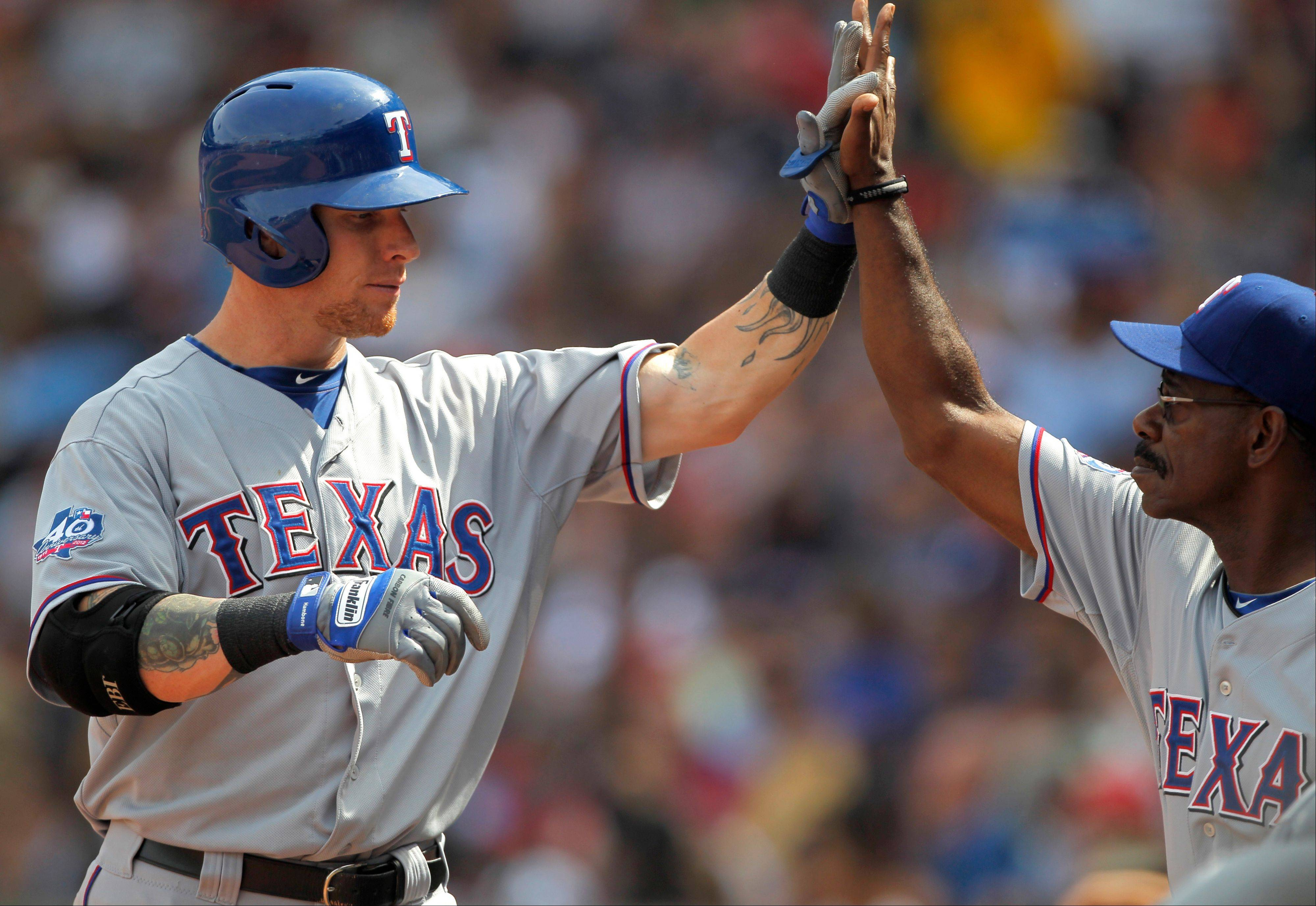 Texas Rangers outfielder Josh Hamilton, left, is welcomed to the dugout by' manager Ron Washington after hitting a two-run home run off a Boston Red Sox pitcher Josh Beckett Wednesday during the fifth inning.