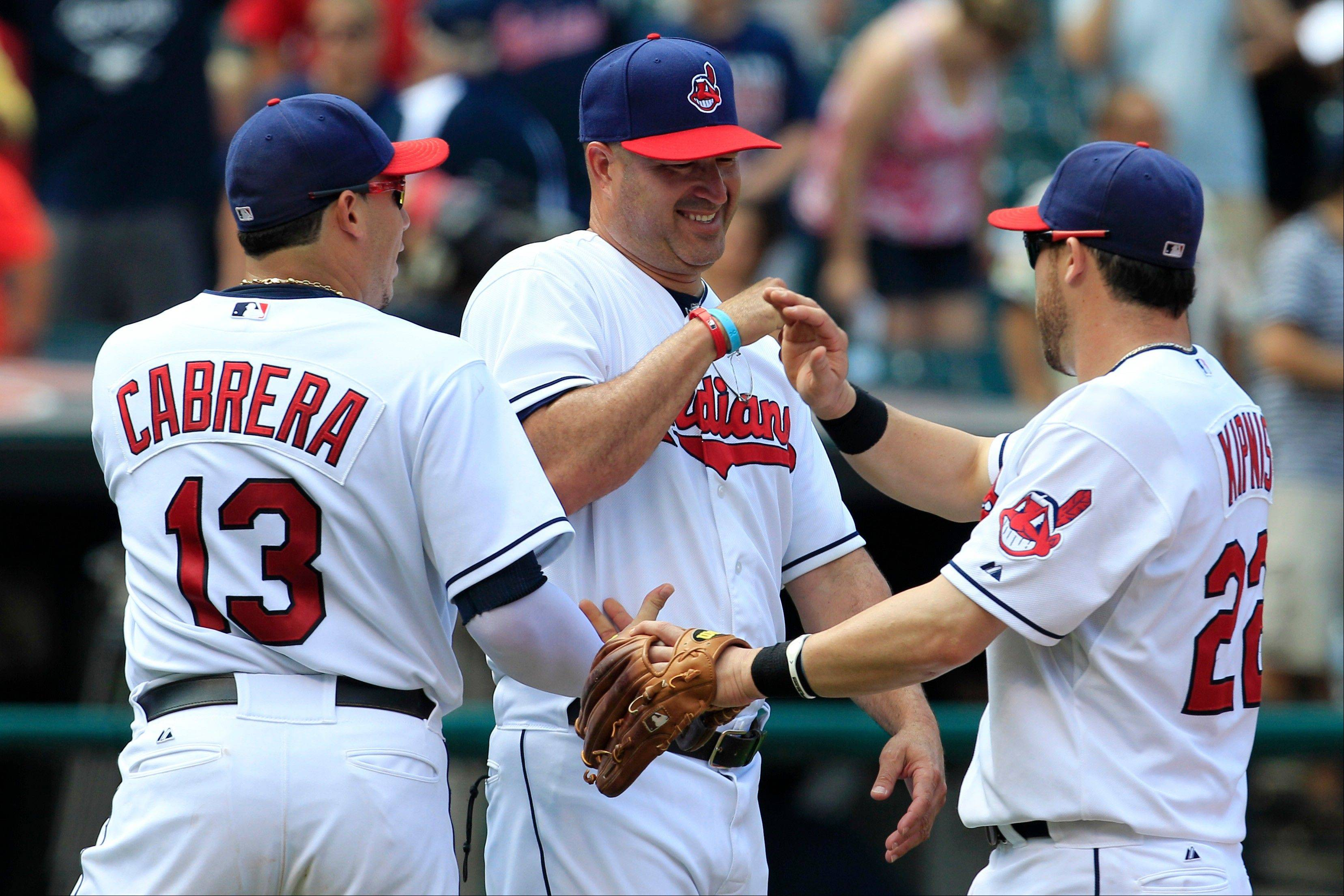 Cleveland Indians manager Manny Acta, center, smiles as he congratulates Asdrubal Cabrera, left, and Jason Kipnis Wednesday after the Indians defeated the Minnesota Twins 6-2 in Cleveland.