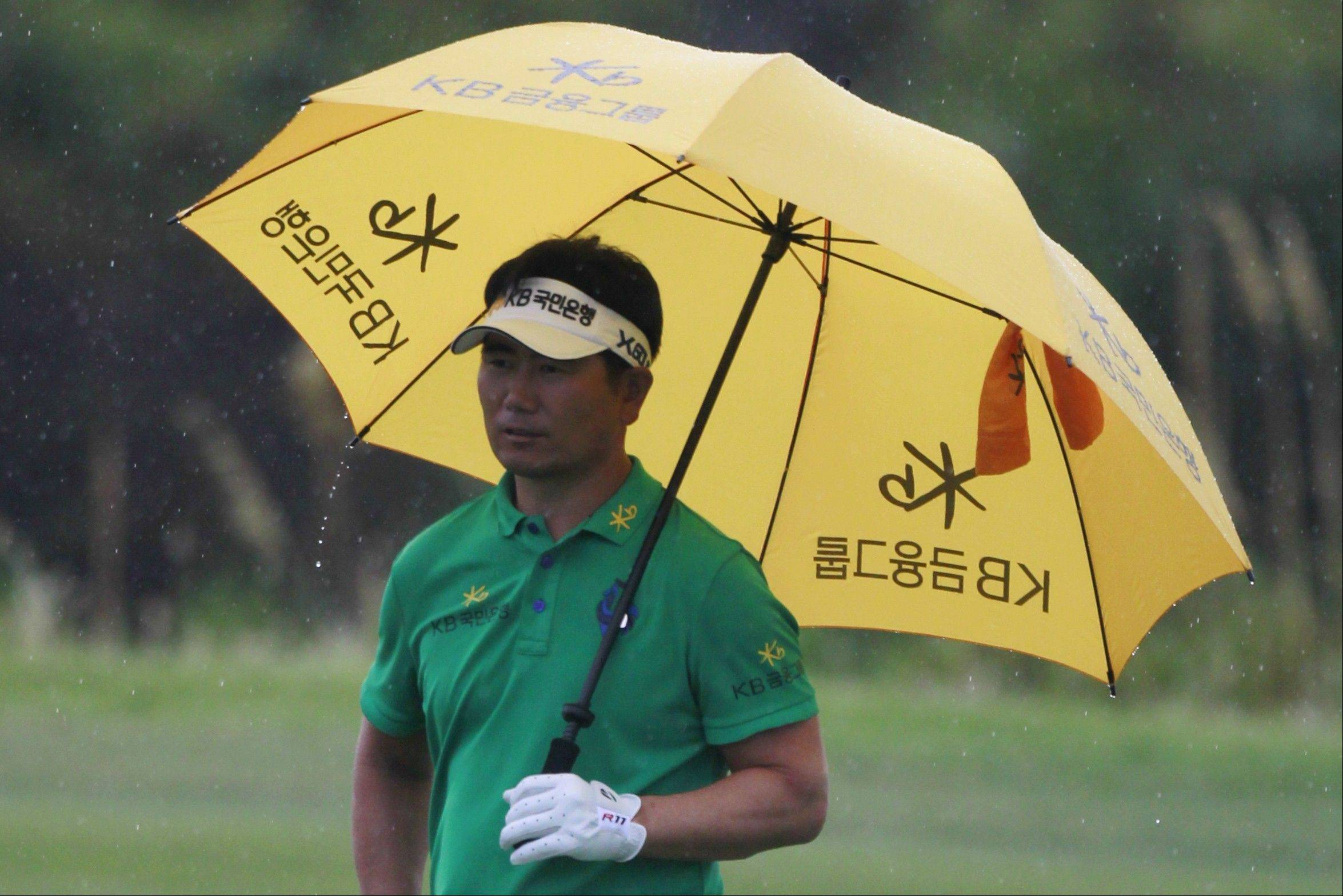 Y.E. Yang waits in the rain Wednesday during a practice round for the PGA Championship. Yang shocked the world when he rallied to beat Tiger Woods at the 2009 PGA Championship.