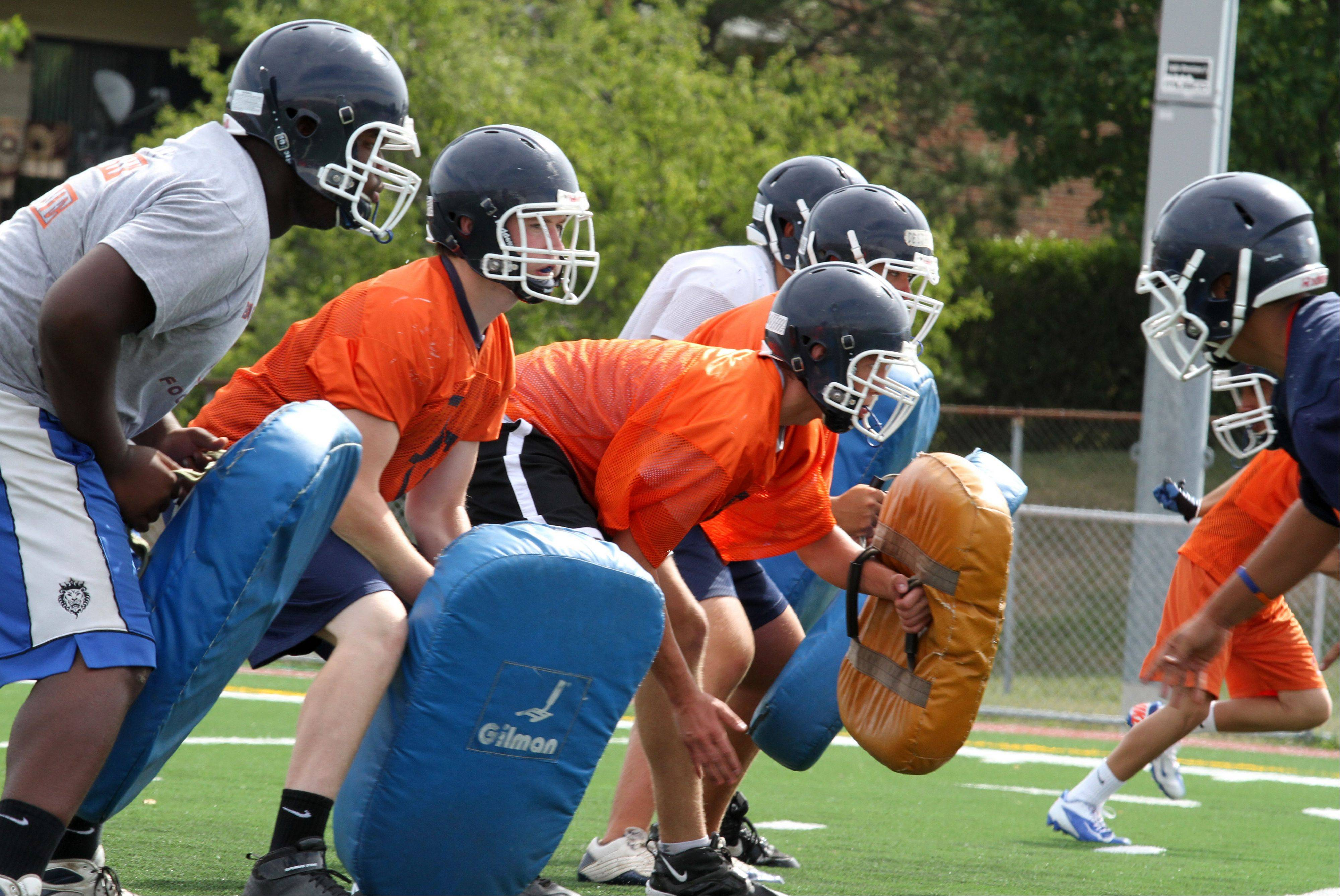Lineman practice with dummy pads during the first day of football practice at Buffalo Grove High School on Wednesday. The first practice was also the team's first chance to play on the new synthetic field installed this summer at BGHS. The first game of the season is Aug. 24.