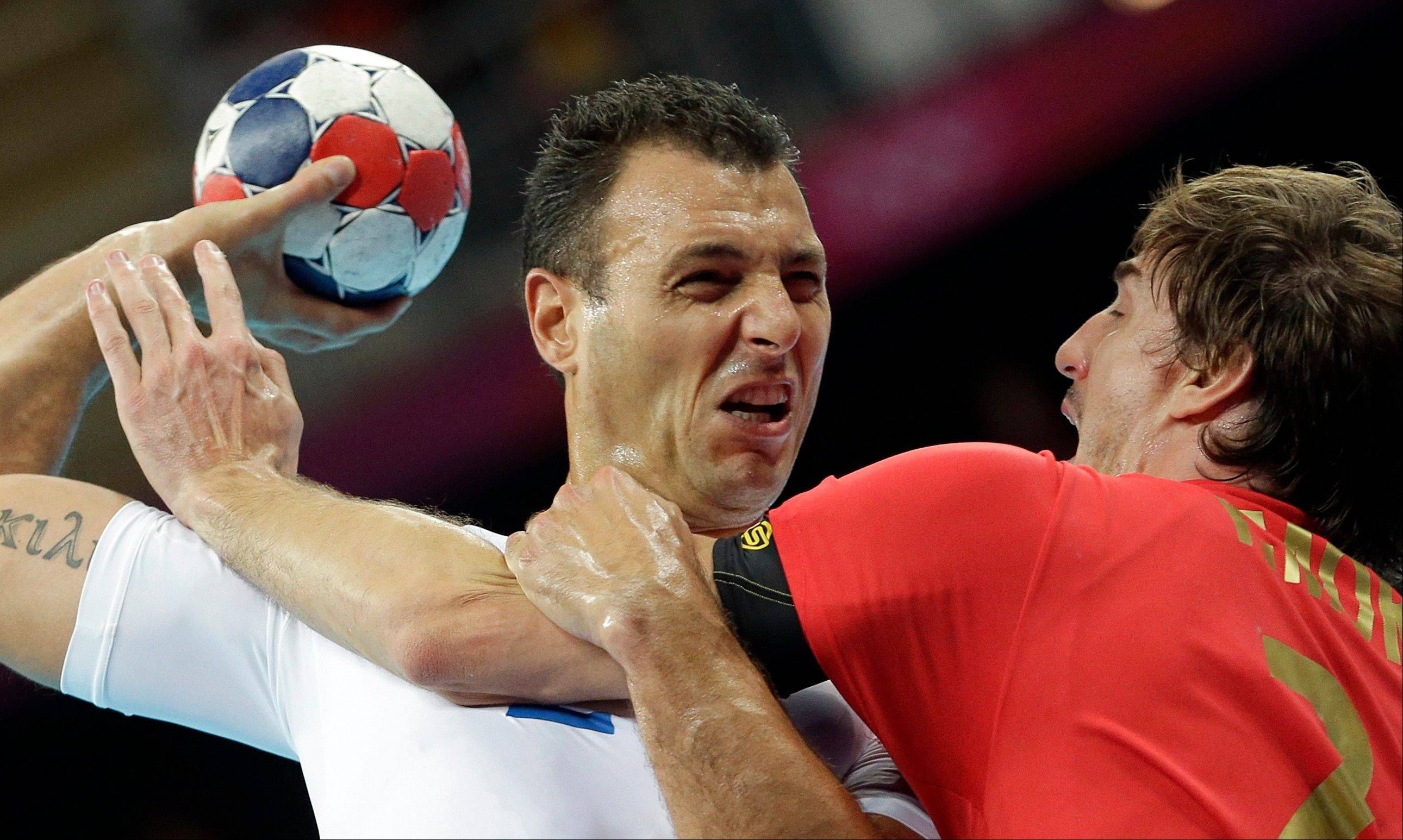 Spain's Viran Morros de Argila, right, and France's Jerome Fernandez challenge during their men's handball quarterfinal match at the 2012 Summer Olympics, Wednesday, Aug. 8, 2012, in London.