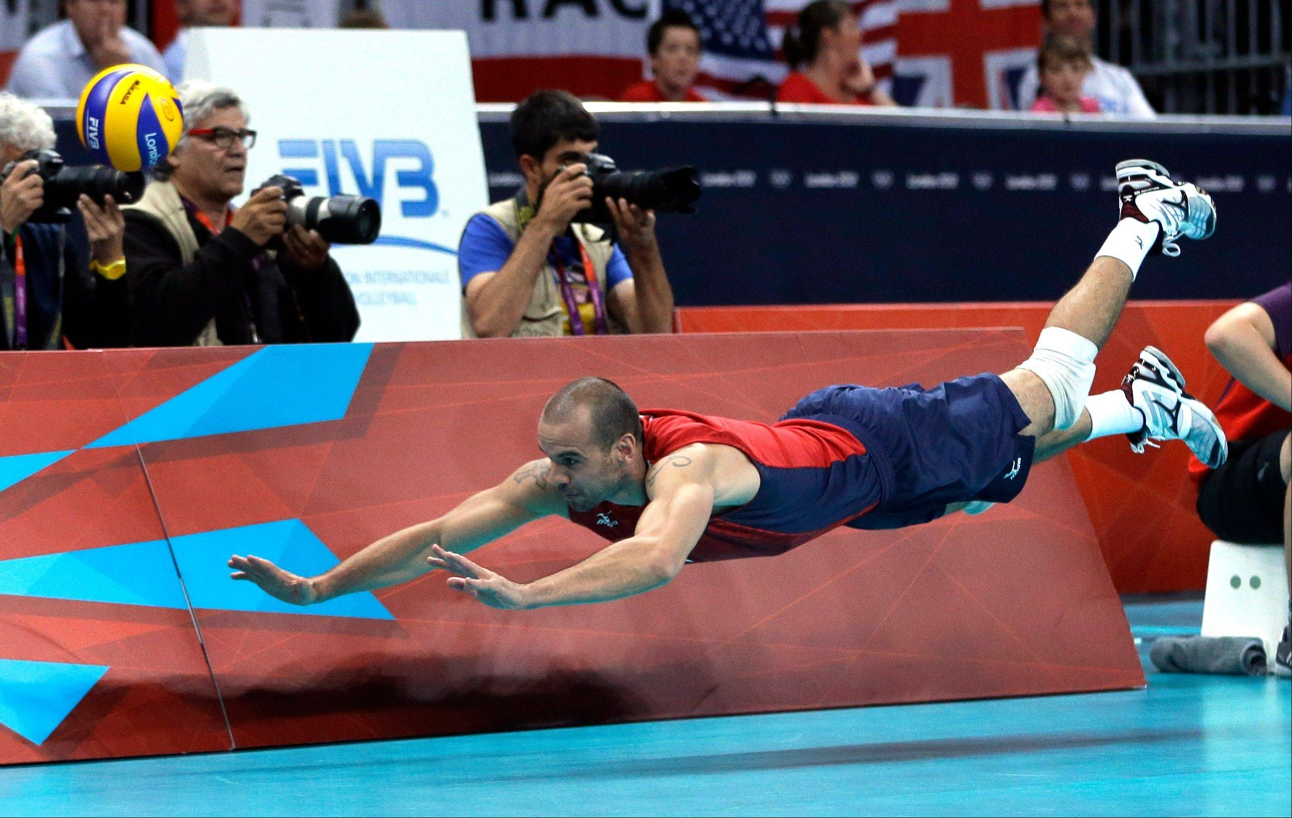 United States' Donald Suxho dives but cannot reach a ball during a men's quarterfinal volleyball match against Italy at the 2012 Summer Olympics, Wednesday, Aug. 8, 2012, in London.