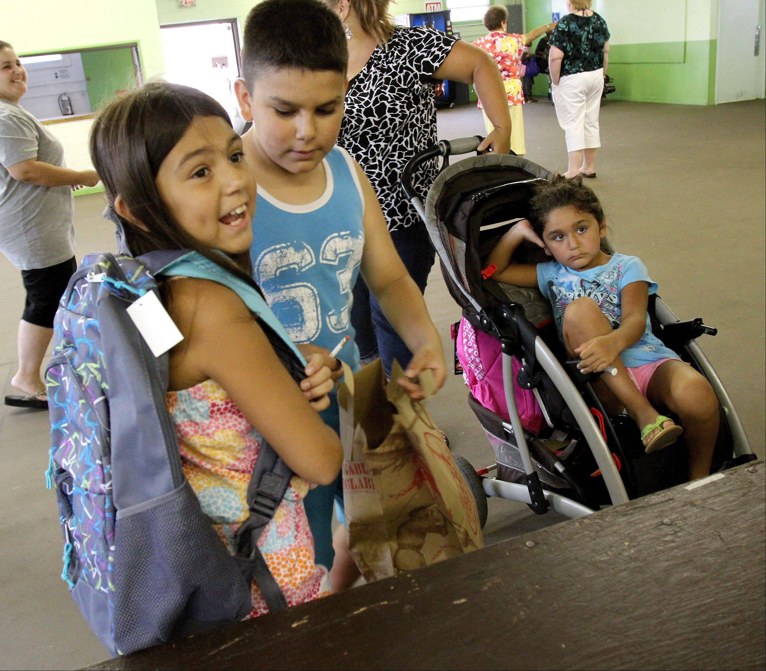 Sofia Zitlal, 9, of Wheaton, tries on her new backpack loaded with school supplies as she and her brother Ryan, sister Angelina and mom Jessical Zitlal visit the Back to School Fair in Wheaton.