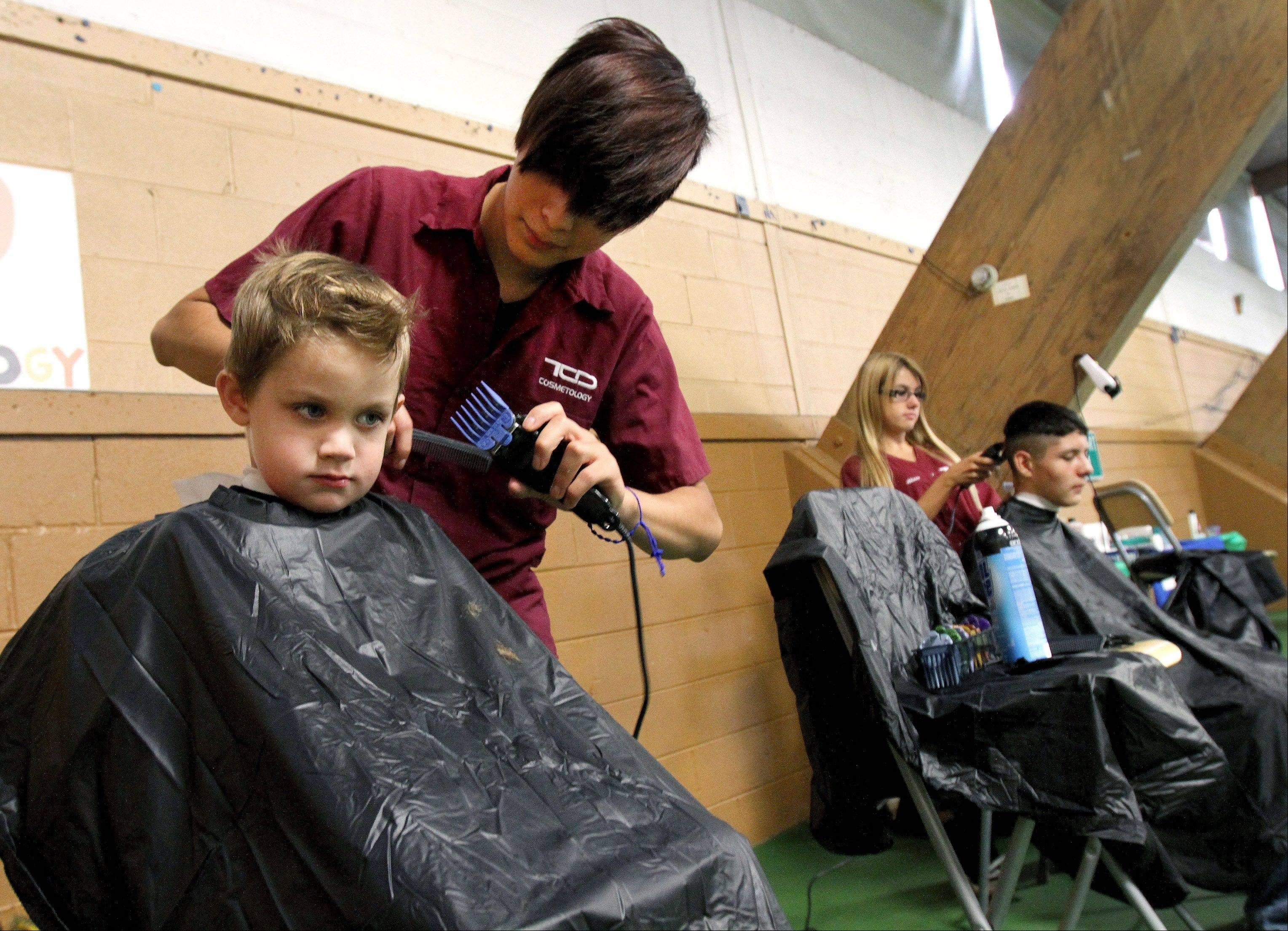 Rogan Packman, 5, of Lombard and Artubio Rubio, 13, of West Chicago get free hair cuts from cosmetology students Alejandro Vasquez and Alison Bednara of the Technology Center of DuPage.