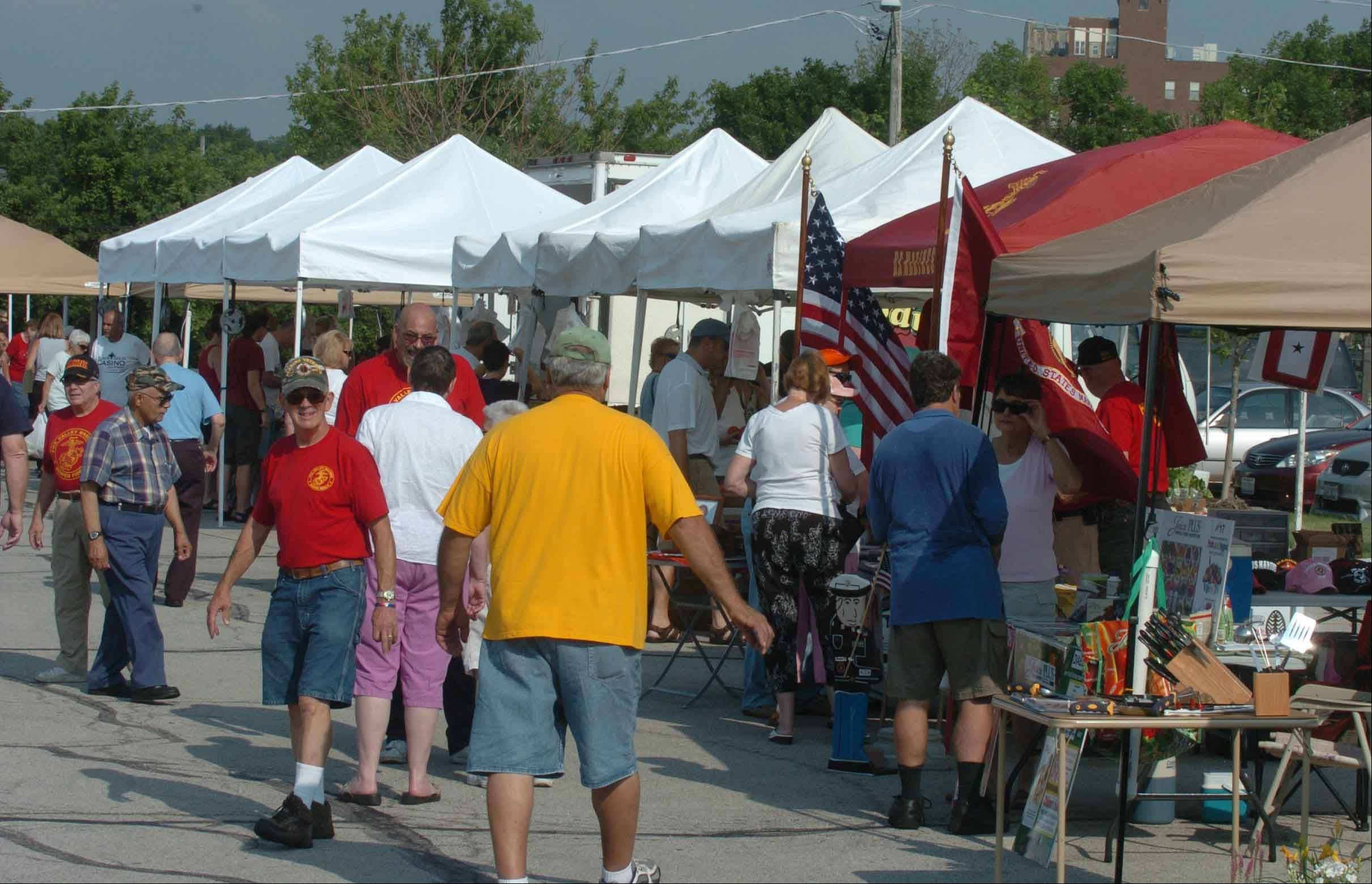 Shoppers browse the Aurora Farmers Market during its 98th year in 2010. The market is celebrating its centennial Saturday with a ceremony at 10 a.m. in North River Street Park at River and Cedar streets.