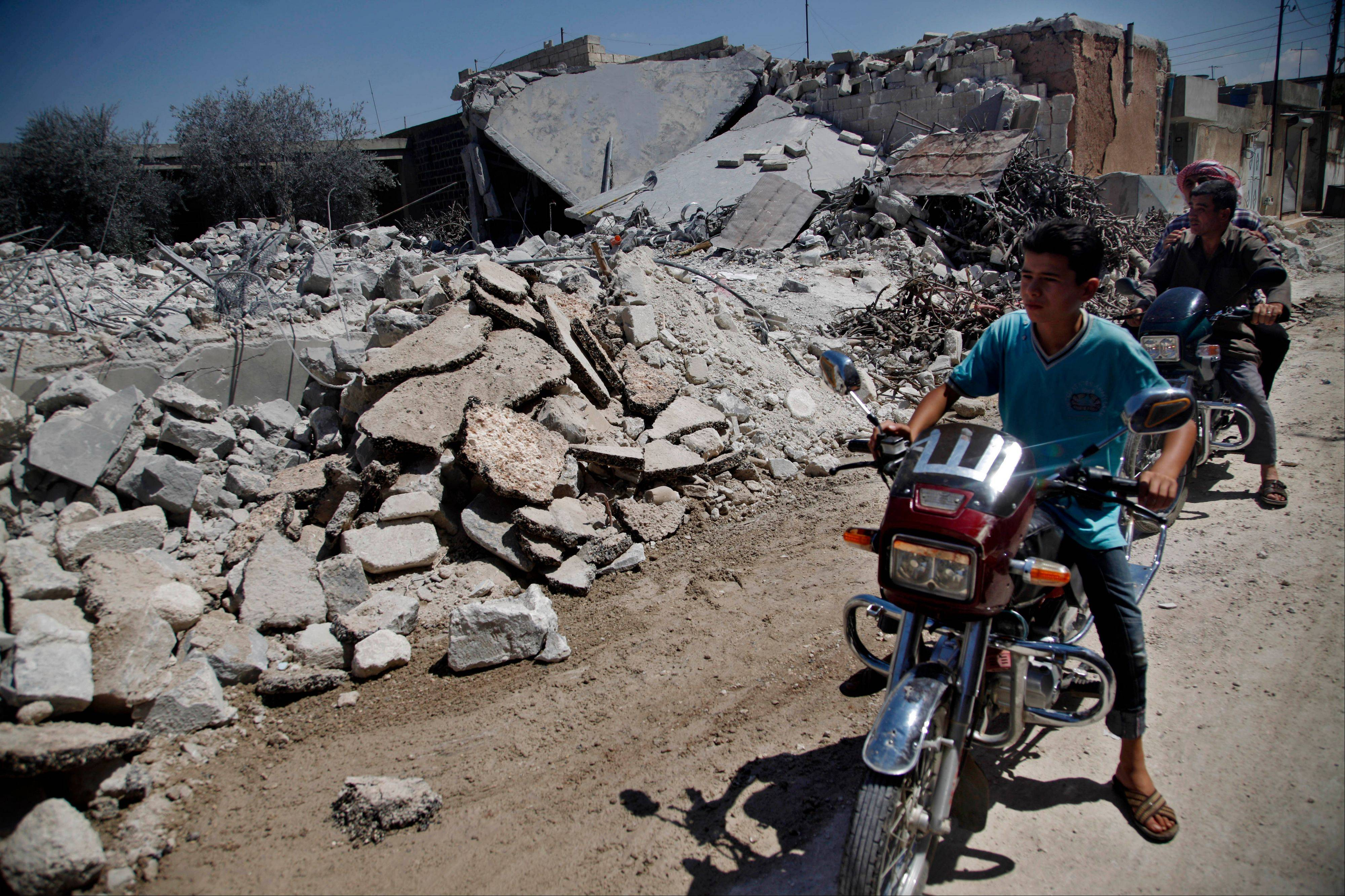 Associated Press Syrians on motorcycles look at the damage of a destroyed house after it was hit by an airstrike killing six Syrians in town of Tal Rifat on the outskirts of Aleppo city, Syria, Wednesday, Aug. 8, 2012.