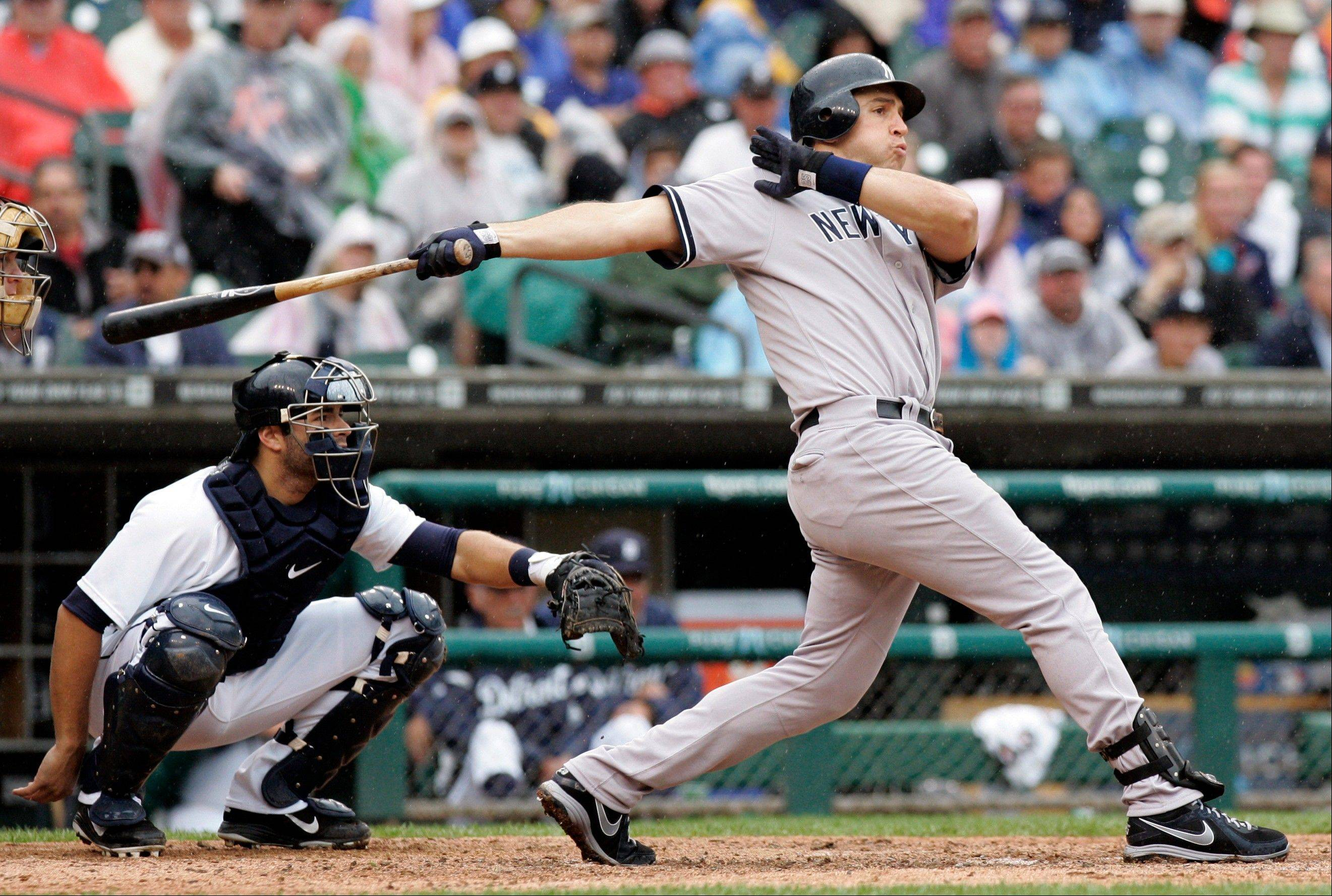 The Yankees� Mark Teixeira hits a solo home run in the eighth inning Thursday in Detroit.