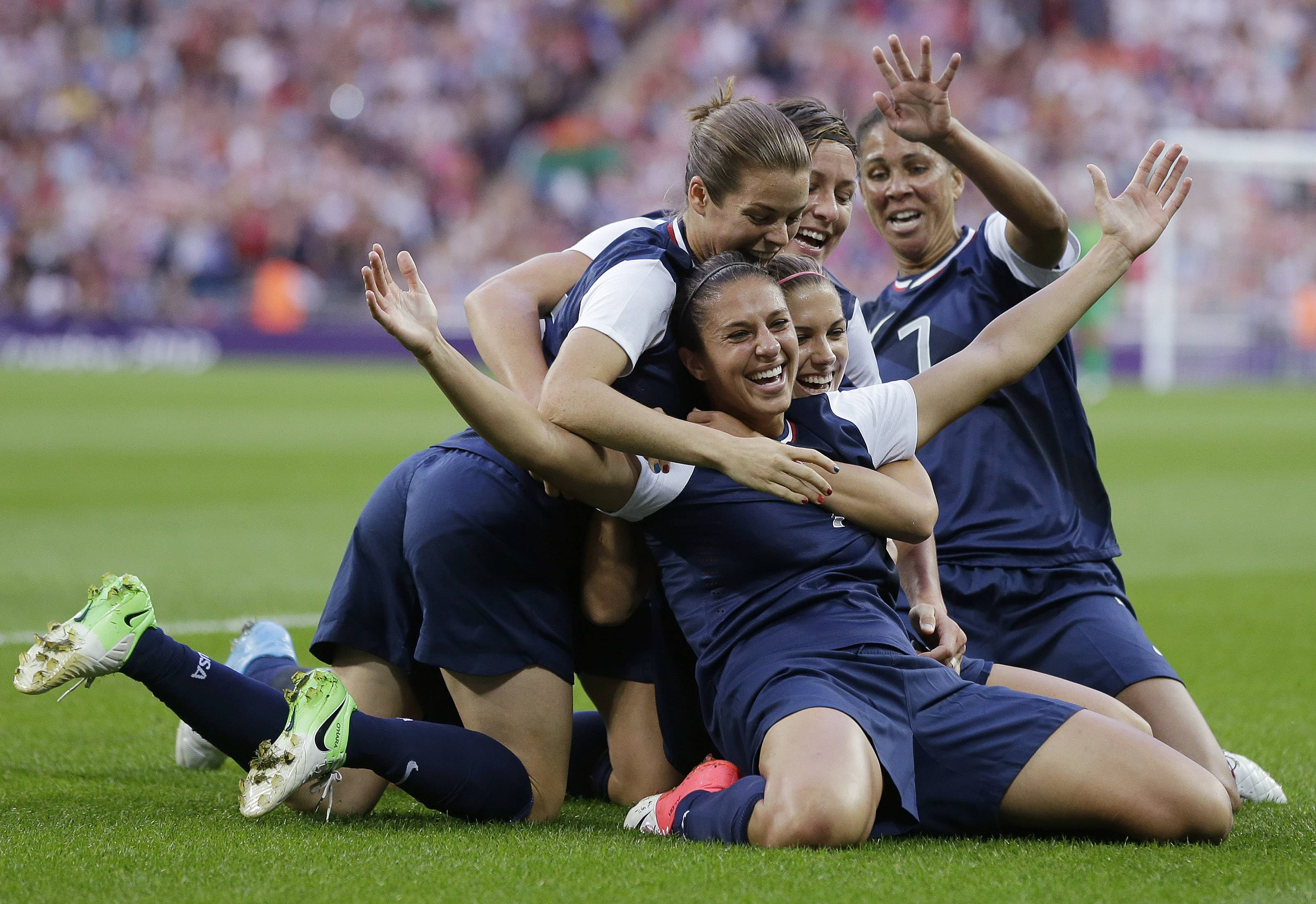 The United States' Carli Lloyd, right, celebrates with teammates after scoring Thursday during the gold medal match against Japan.