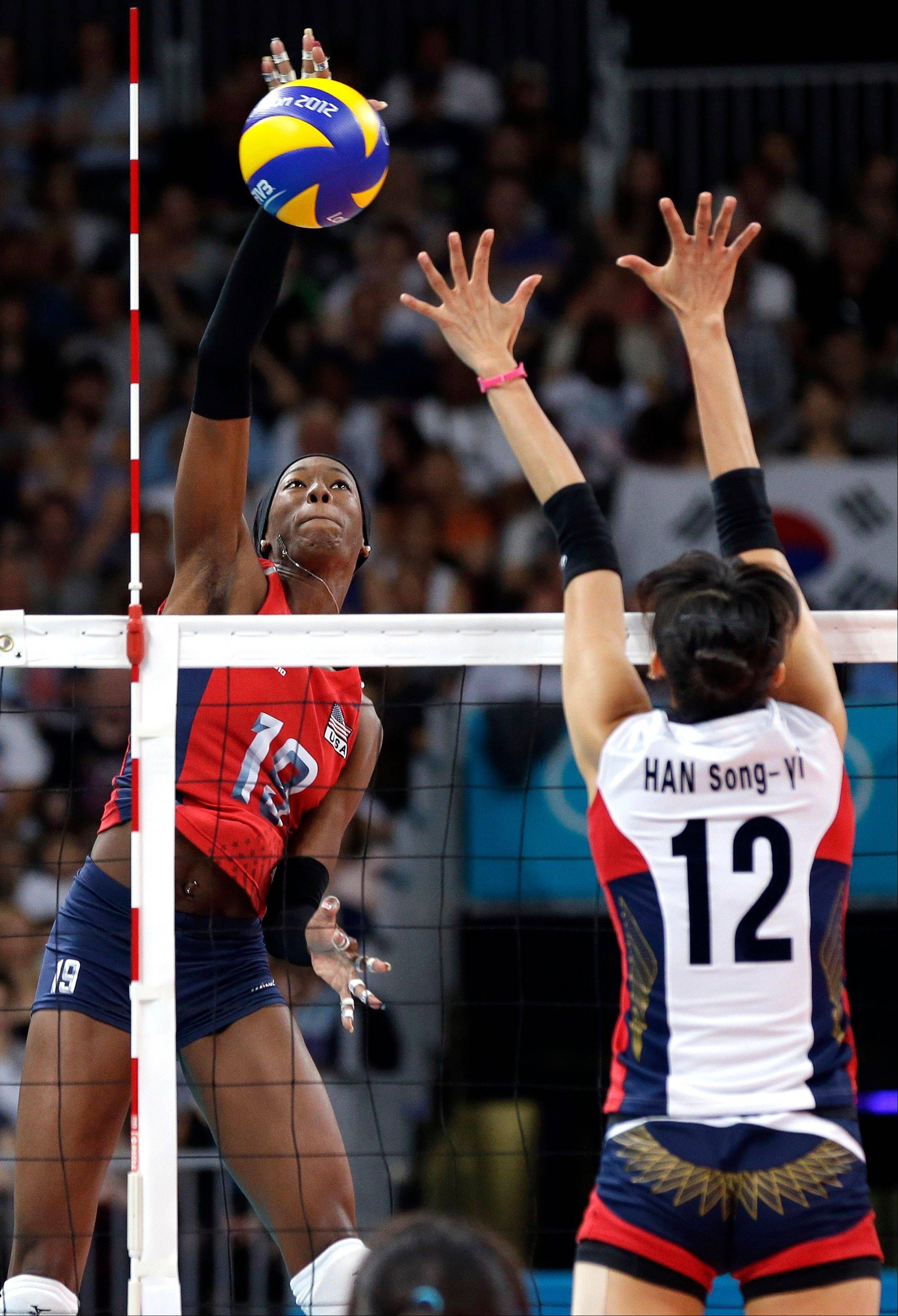 USA's Destinee Hooker (19) goes up for a smash in front of South Korea's Han Song-yi (12) during a women's volleyball semifinal match at the 2012 Summer Olympics Thursday, Aug. 9, 2012, in London. (AP Photo/Chris O'Meara)