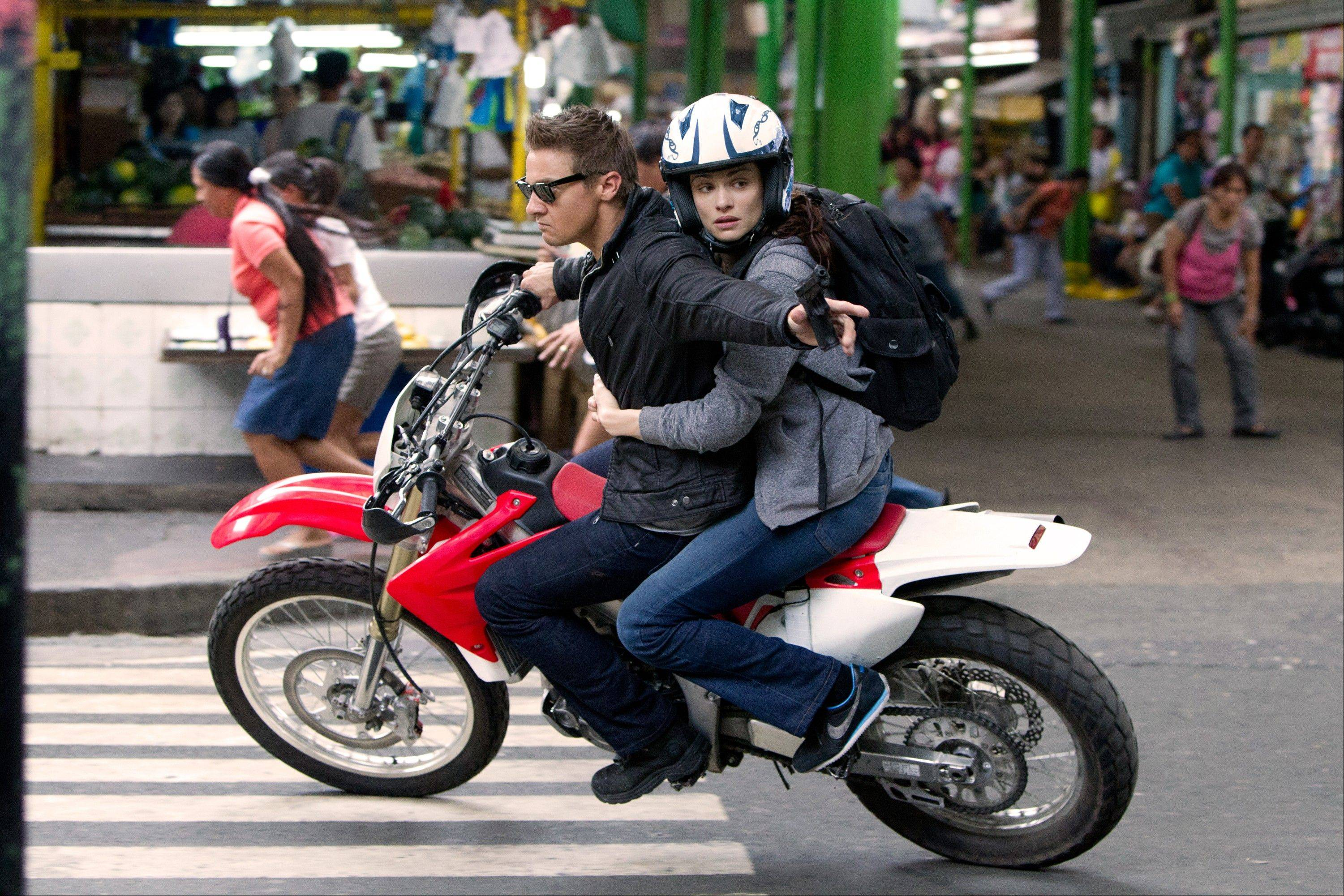"Agent Aaron Cross (Jeremy Renner) escapes assassins with Dr. Marta Shearing (Rachel Weisz) in the action thriller sequel ""The Bourne Legacy."""