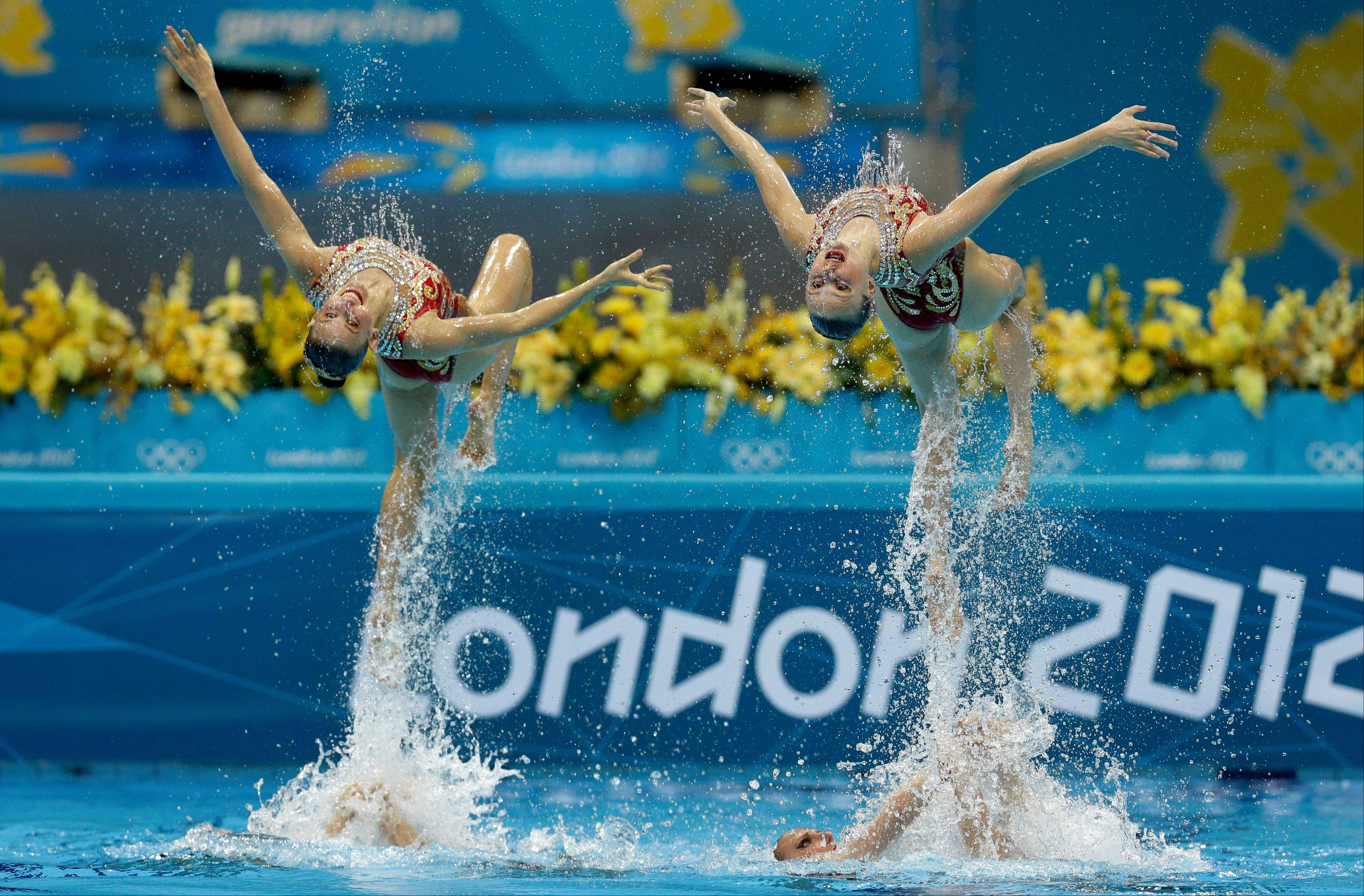 Members of the team of Russia are thrown up in the air during the women's team synchronized swimming technical routine at the Aquatics Centre in the Olympic Park during the 2012 Summer Olympics in London, Thursday, Aug. 9, 2012.