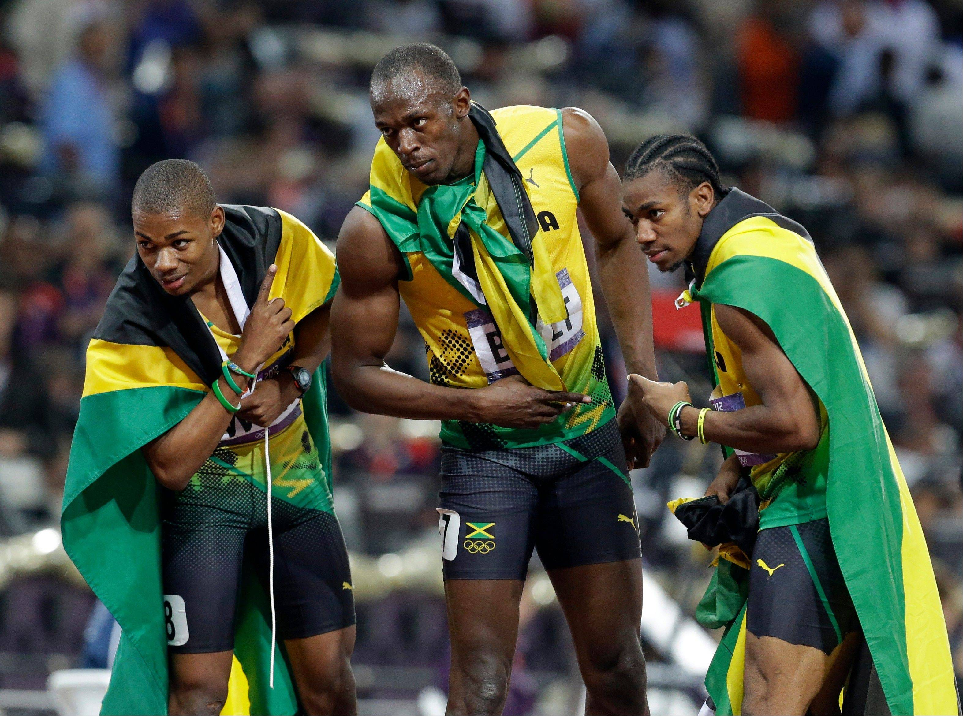 Jamaica's gold medal winner Usain Bolt, center, celebrates with his teammate Warren Weir, left, and Yohan Blake after the men's 200-meter final during the athletics in the Olympic Stadium at the 2012 Summer Olympics, London, Thursday, Aug. 9, 2012.