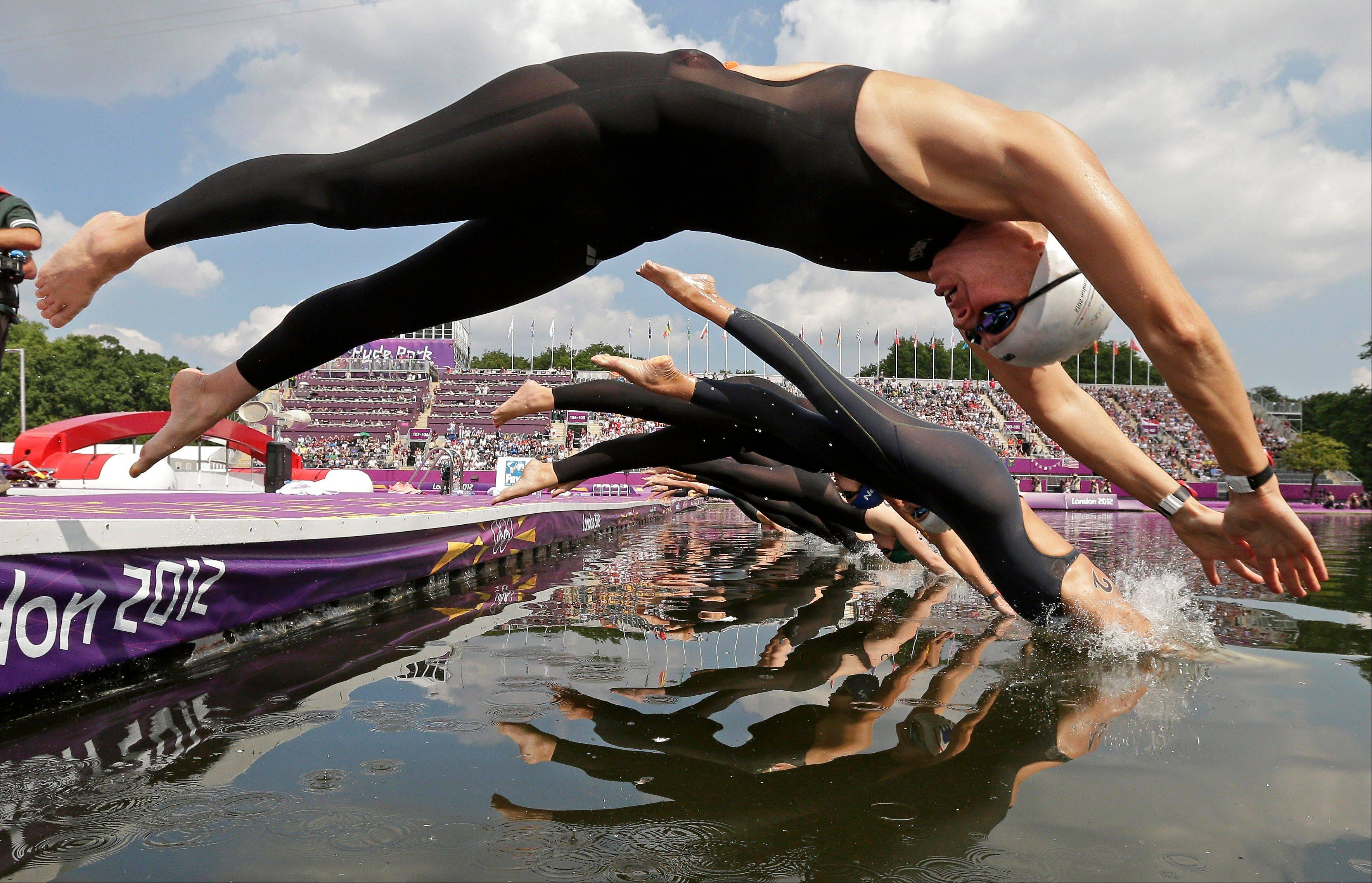 Germany's Angela Maurer, front, and other athletes dive into the Serpentine at Hyde Park as they compete in the women's marathon swimming competition at the 2012 Summer Olympics Thursday, Aug. 9, 2012, in London.