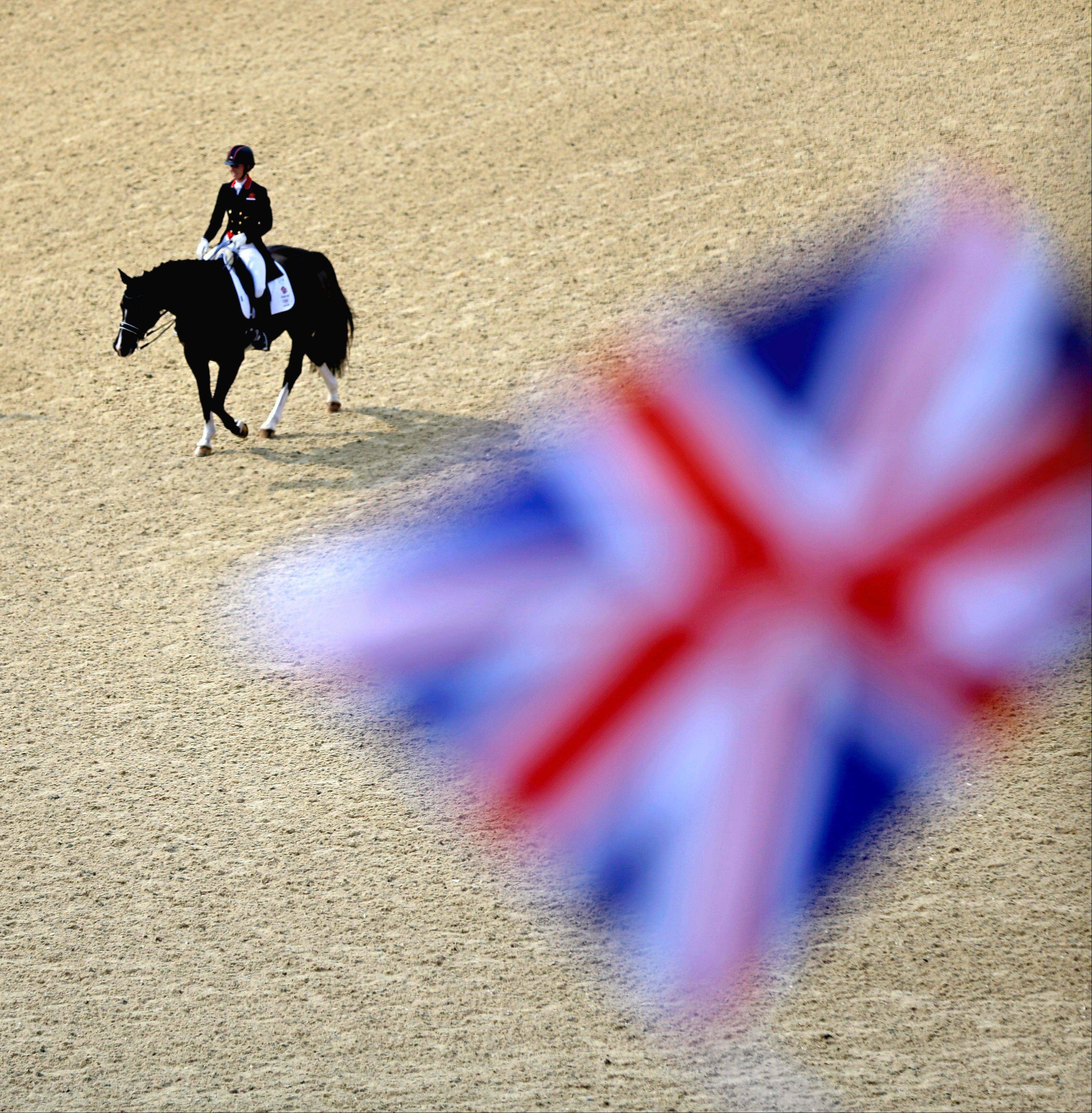 Charlotte Dujardin, of Great Britain, exits the arena after completing her routine with her horse Valegro to win the gold medal in the equestrian dressage individual competition at the 2012 Summer Olympics, Thursday, Aug. 9, 2012, in London.