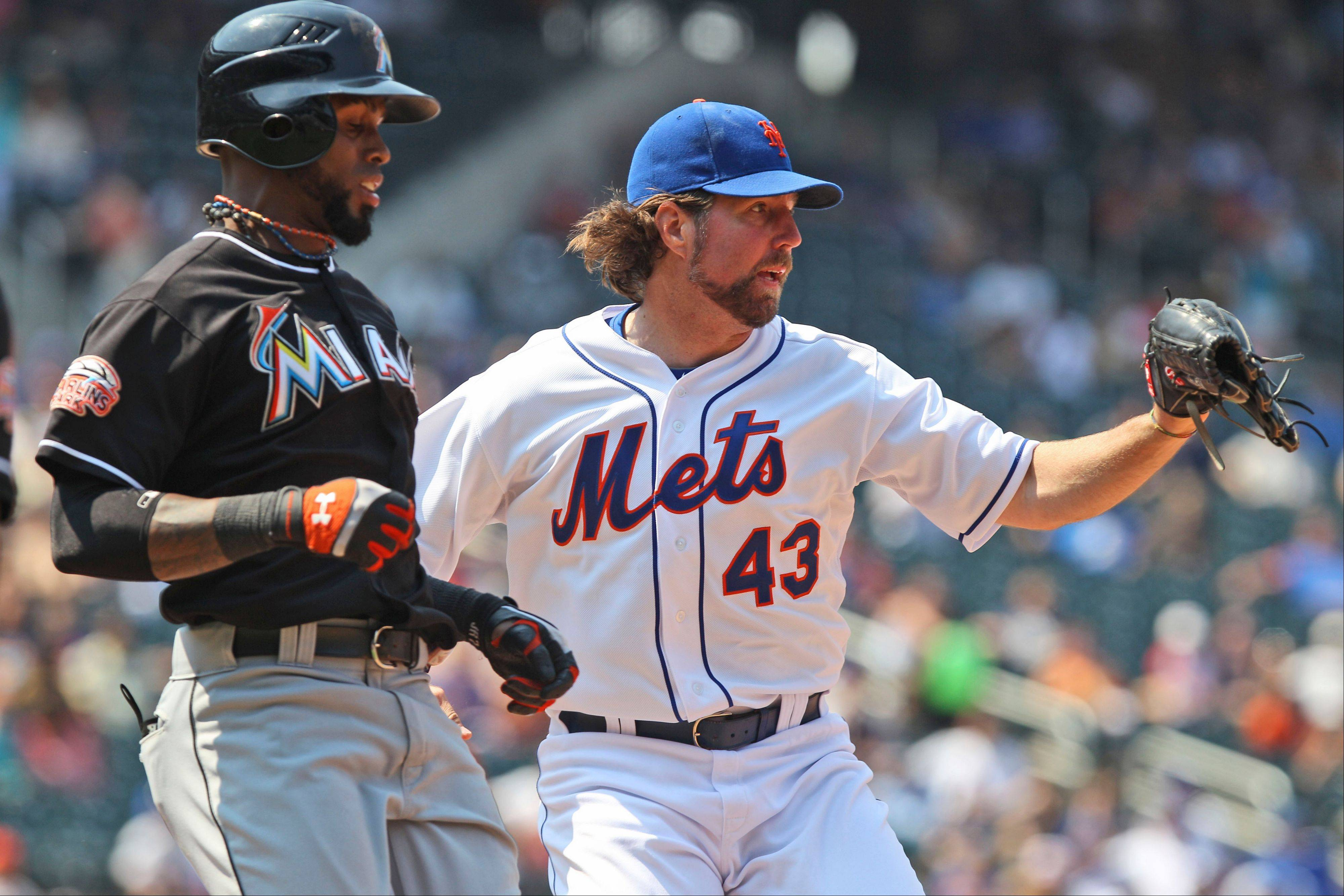 Mets starting pitcher R.A. Dickey, right, beats Miami's Jose Reyes to first base for an out during the eighth inning Thursday in New York.