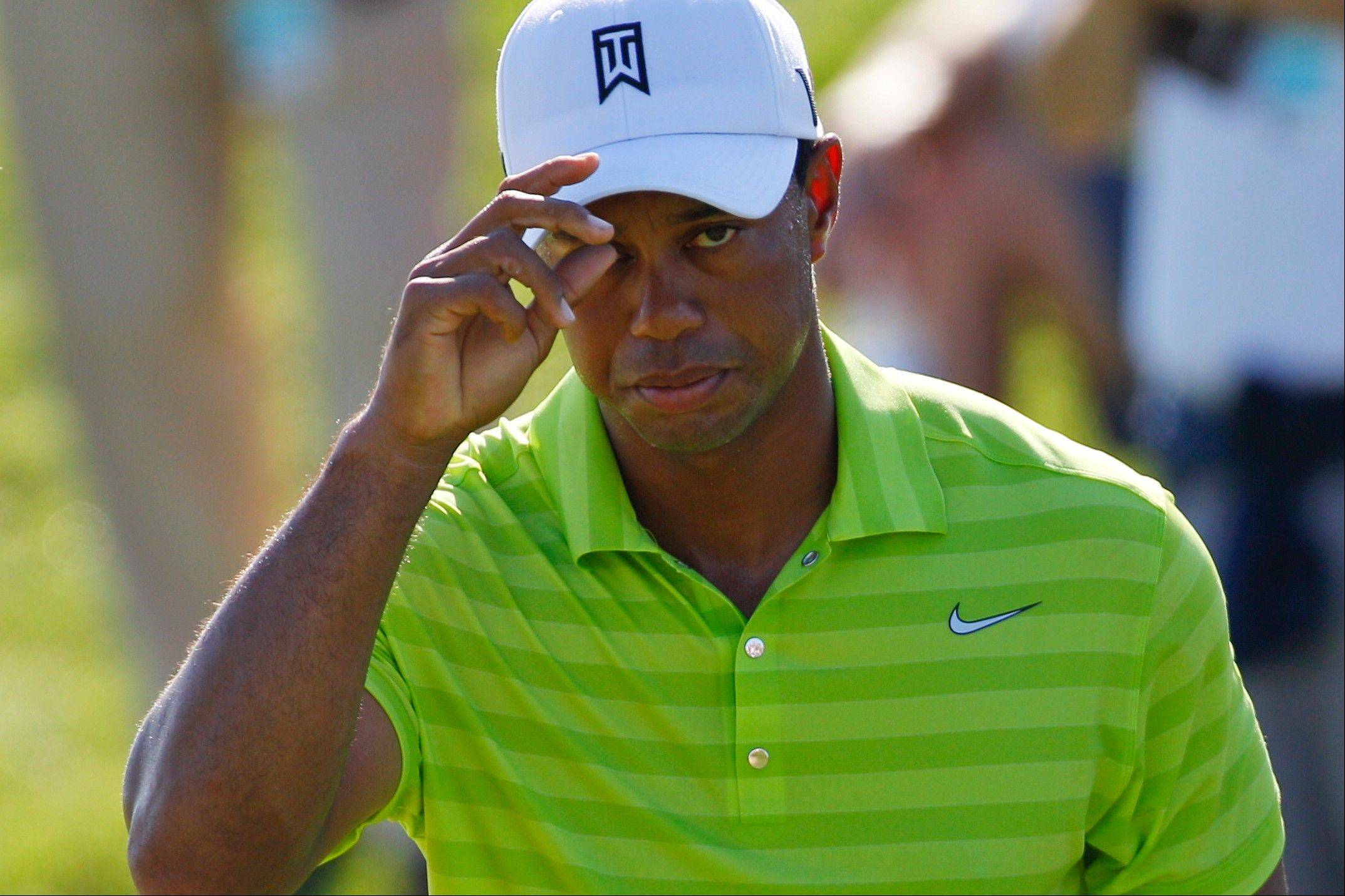 Tiger Woods tips his hat to the gallery on the 13th hole Thursday during the first round of the PGA Championship.